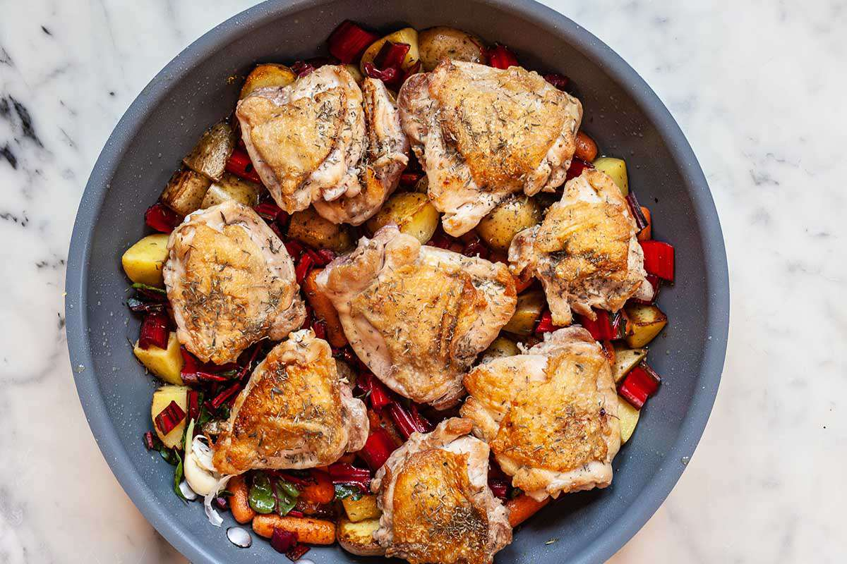 A grey skillet with crispy chicken thighs, chopped potatoes, baby carrots and swiss chard stems cooking inside.