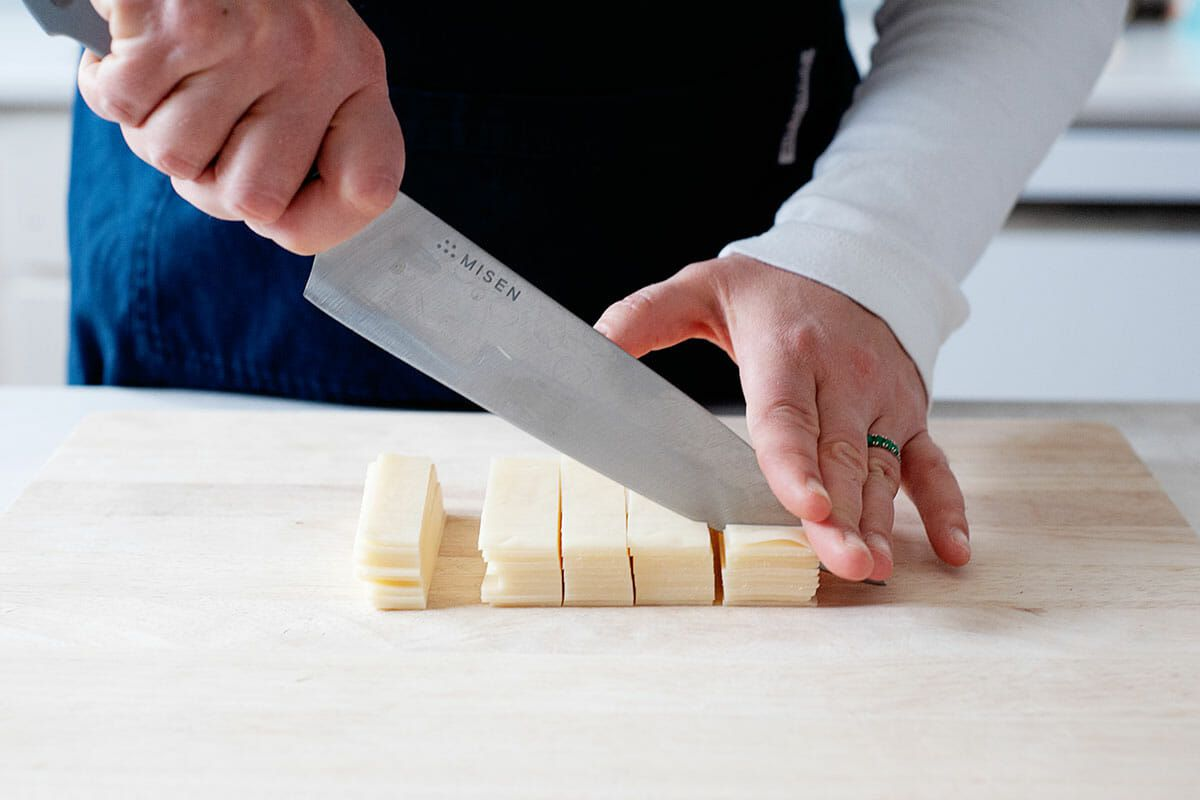 A person with a blue apron and long sleeved white shirt is holding a chef's knife and chopping swiss cheese on a wooden cutting board.