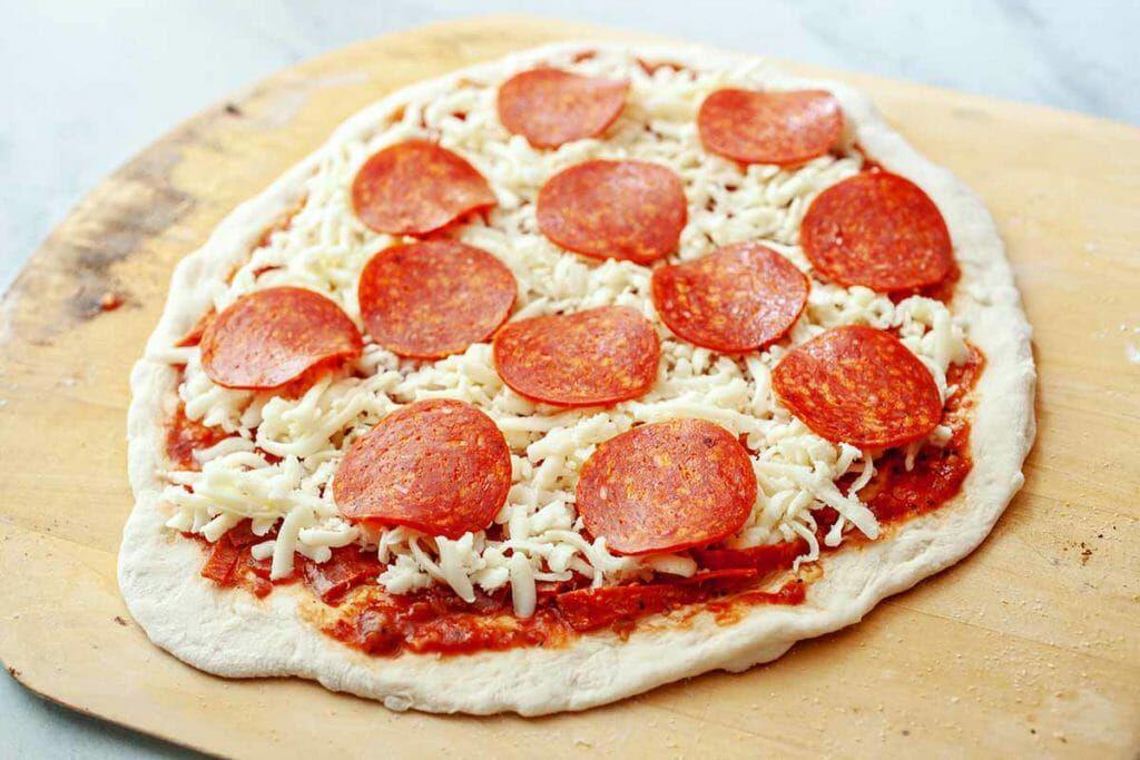 Assembling homemade pepperoni pizza