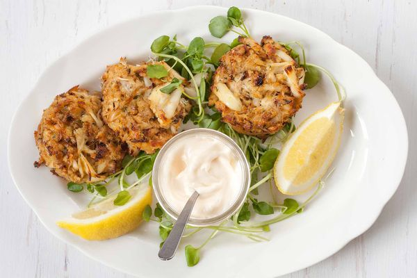 Maryland Crabcakes wtih greens and lemon wedges on a white plate wtih mayo