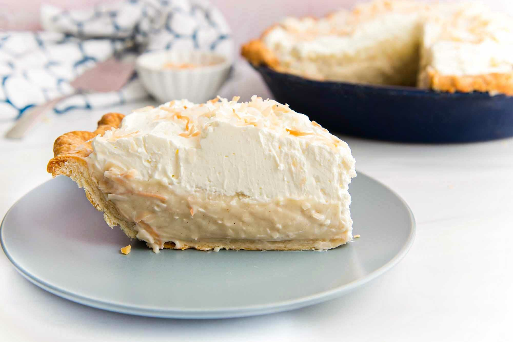 Side view of toasted coconut cream pie with a crisp crust, coconut filling and topped with a thick layer of whipping cream. The rest of the pie is visible behind the plate.