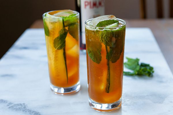 Two tall glasses of Pimms cup cocktail with slices of cucumber, mint leaves and ice. Mint leaves and Pimms no 1 are behind the glasses.