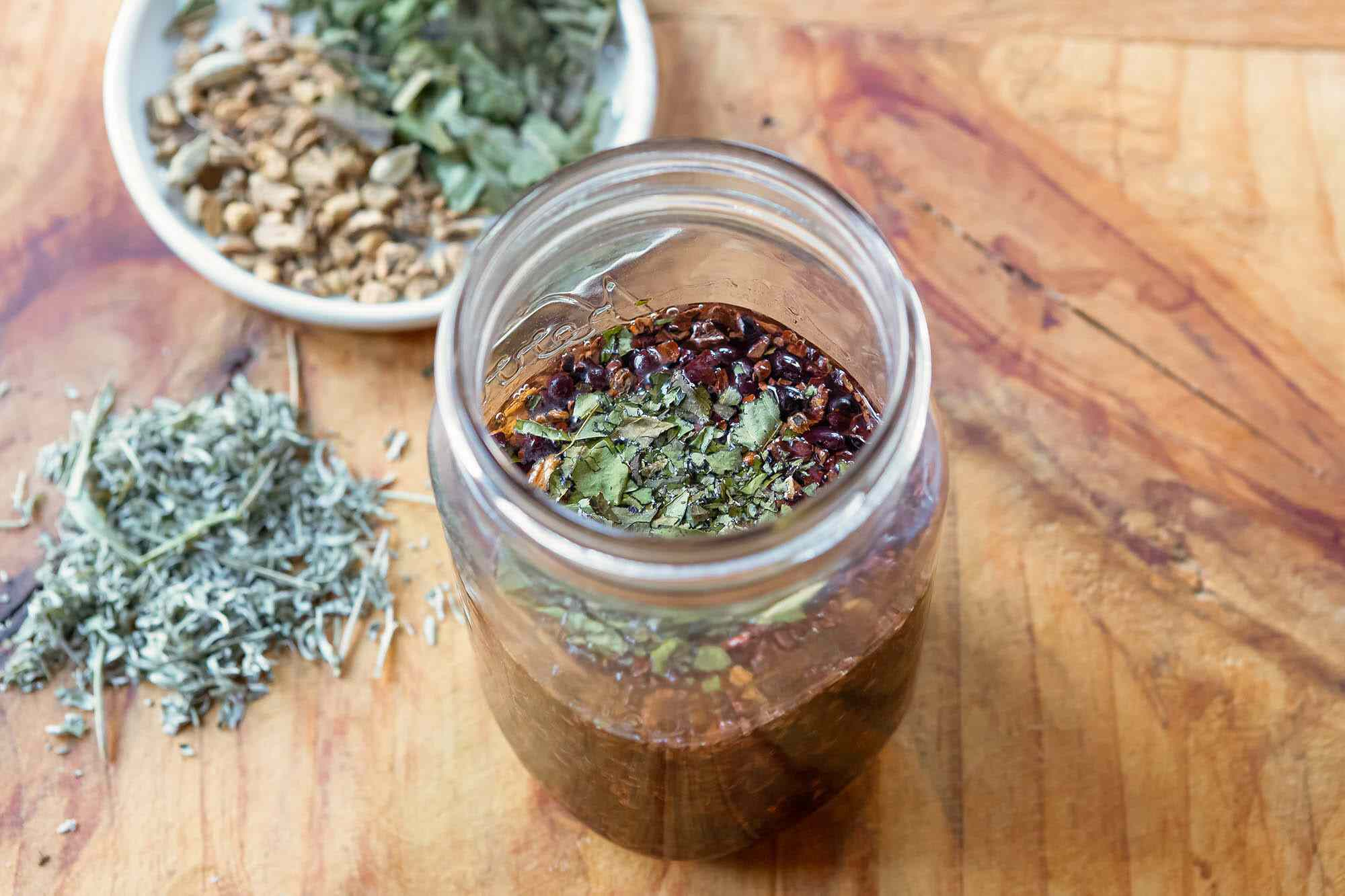 A mason jar with herbs and roots for homemade bitters.