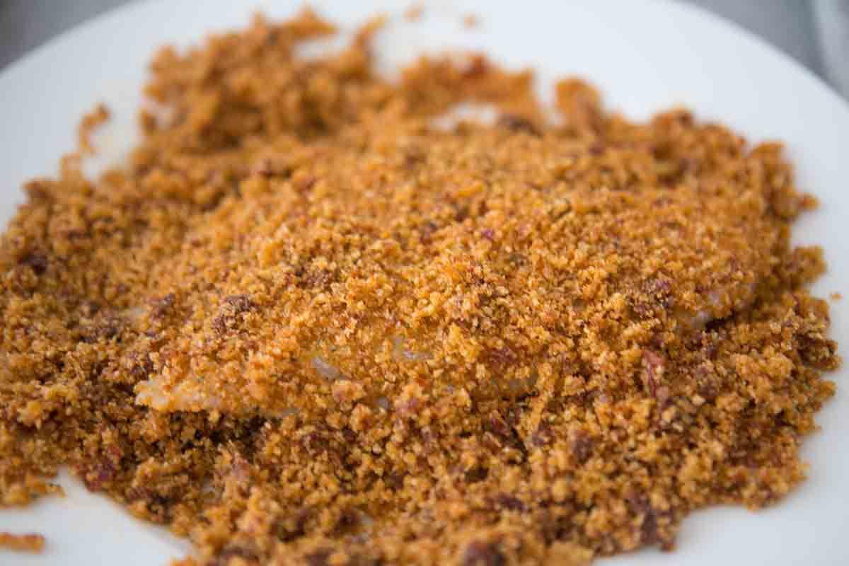 press breading mixture over tilapia fillet