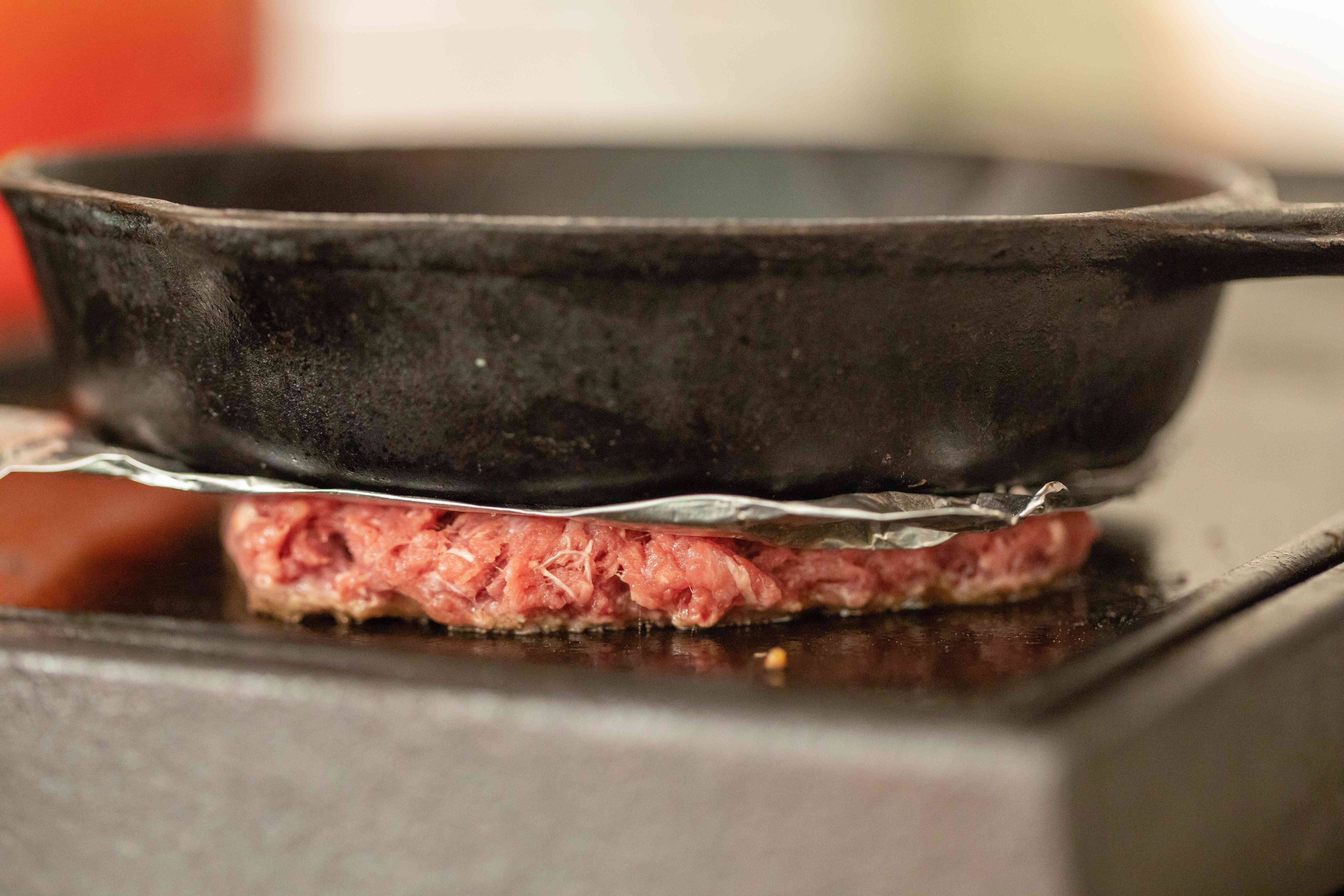 Pressing a burger on a griddle with a cast iron pan