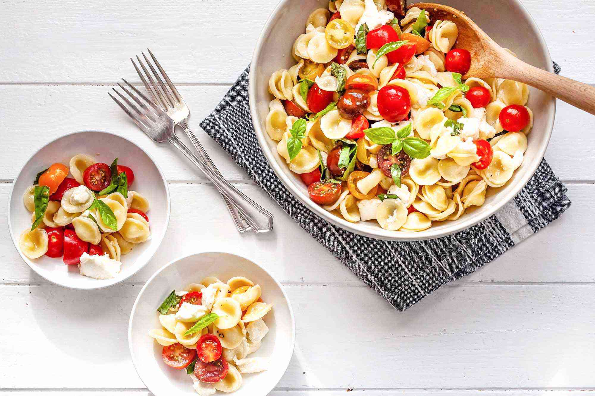 How to Make Caprese Pasta Salad - bowl of caprese salad with pasta with two smaller bowls and forks