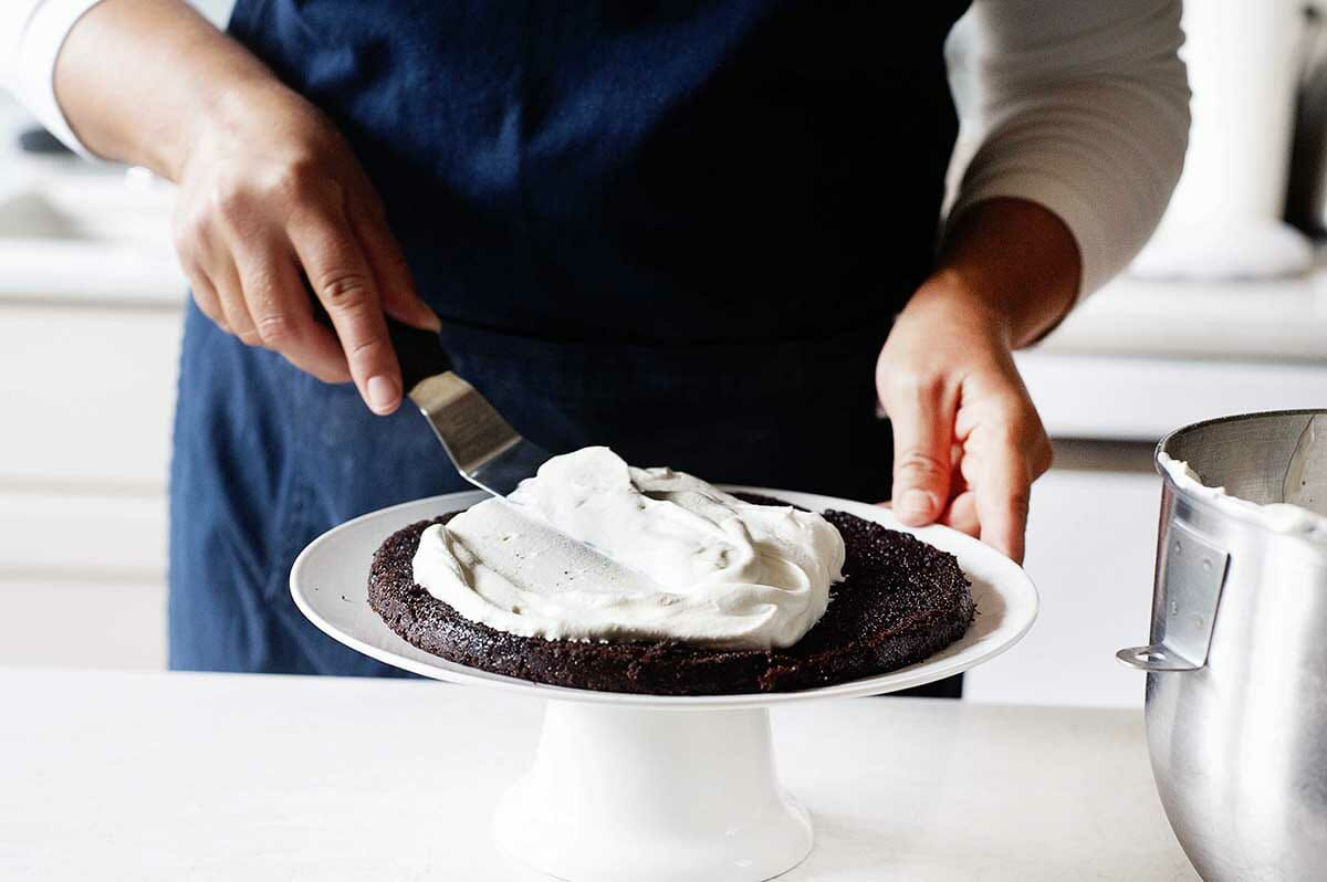 Authentic Black Forest Cake with the first chocolate layer getting whipped cream spread on top.