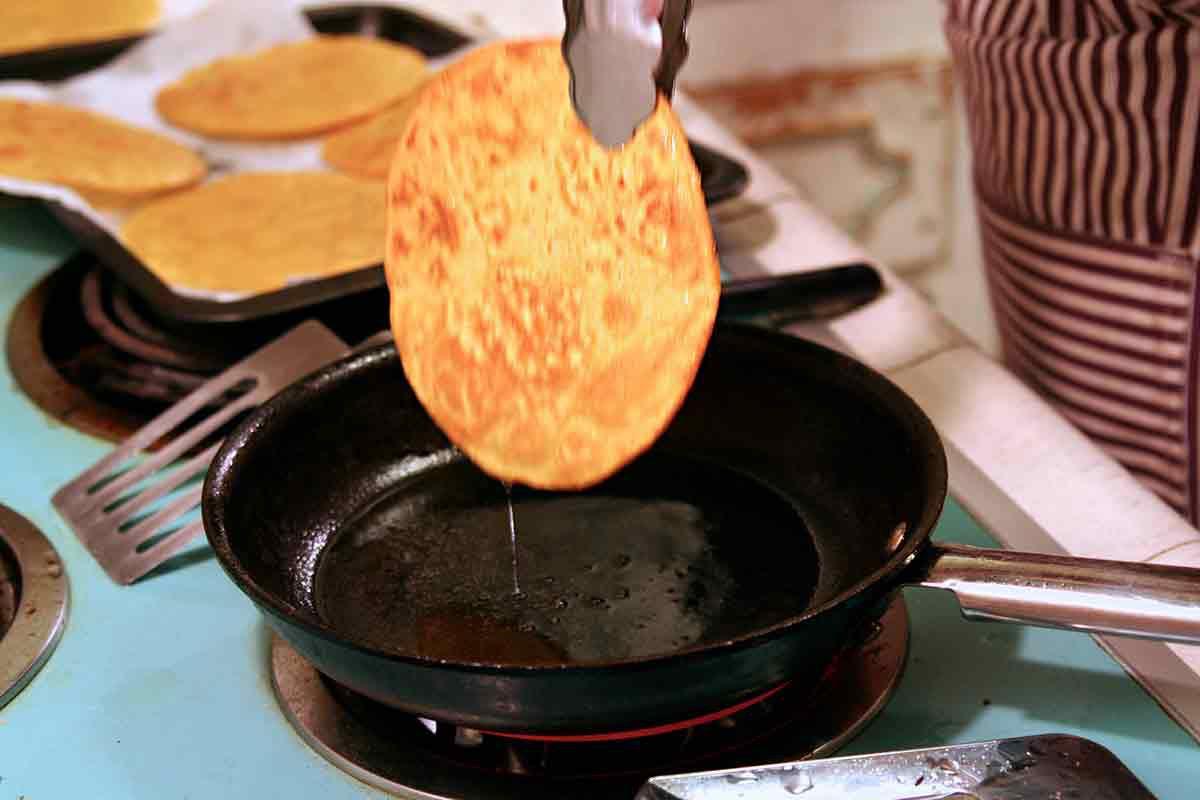 lift tostada fried tortilla out of pan