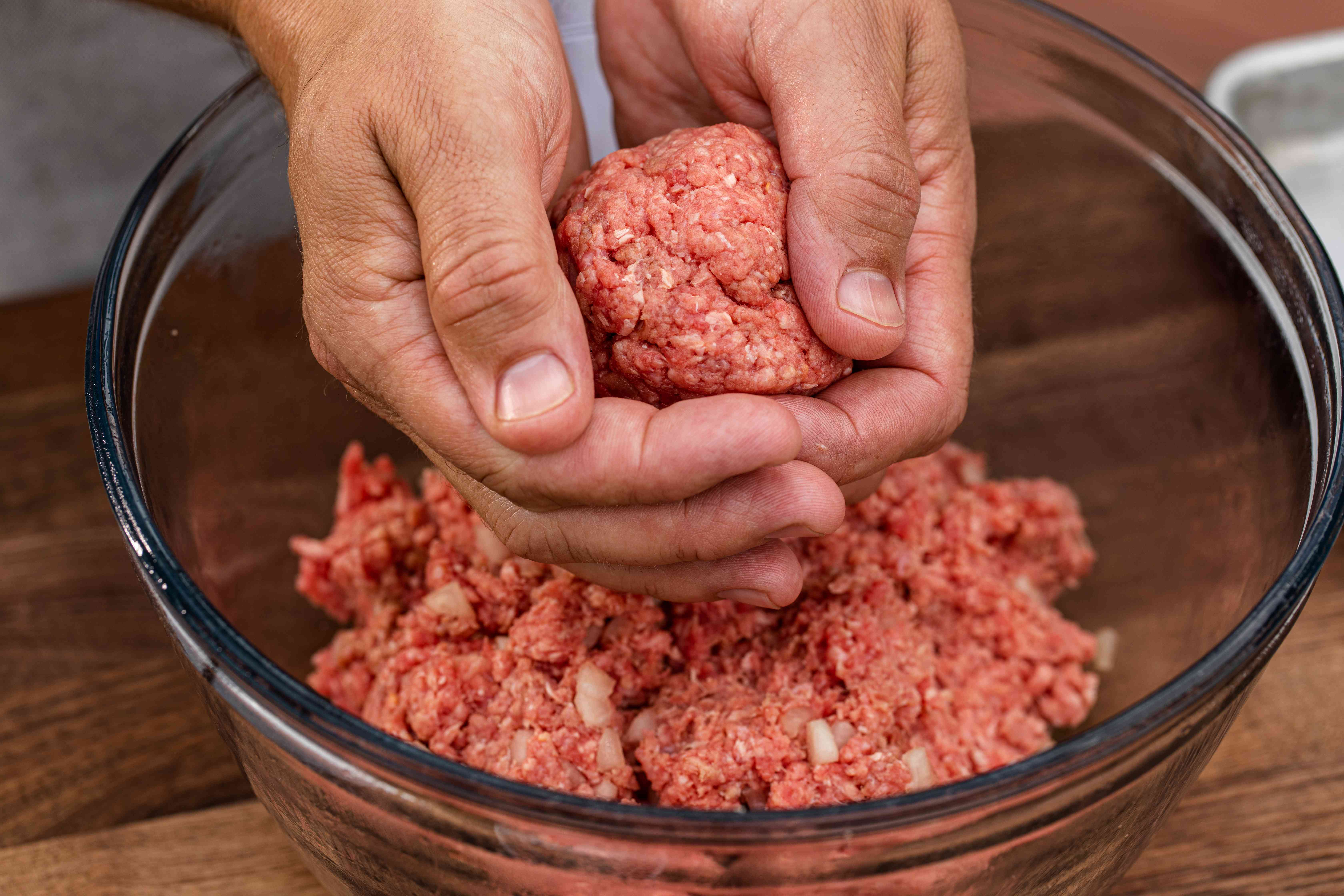 Forming balls of ground beef to make a classic bacon cheeseburger