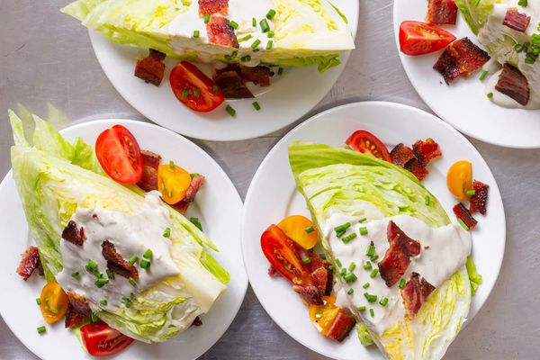 Three wedge salads on white plates. The salads have blue cheese dressing, halved tomatoes and bacon on top.