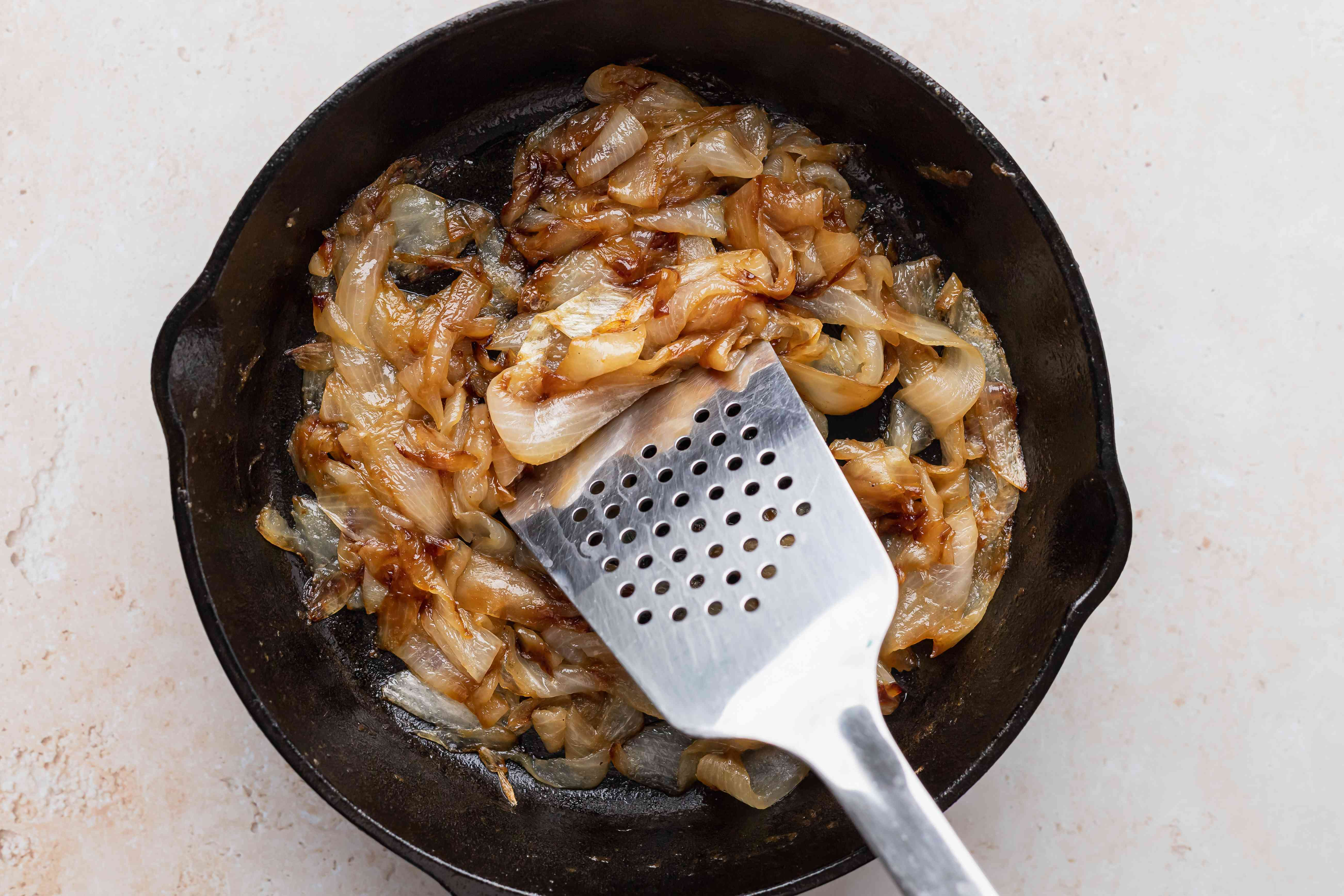A metal spatula stirring onions in a cast iron skillet to show how to saute onions.