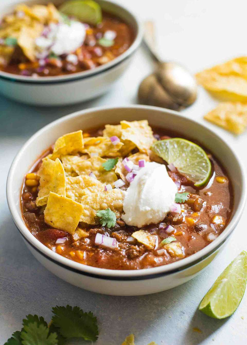 Crockpot taco soup made with beans, ground beef, beans, and corn, and topped with tortilla chips, sour cream, and lime wedges.