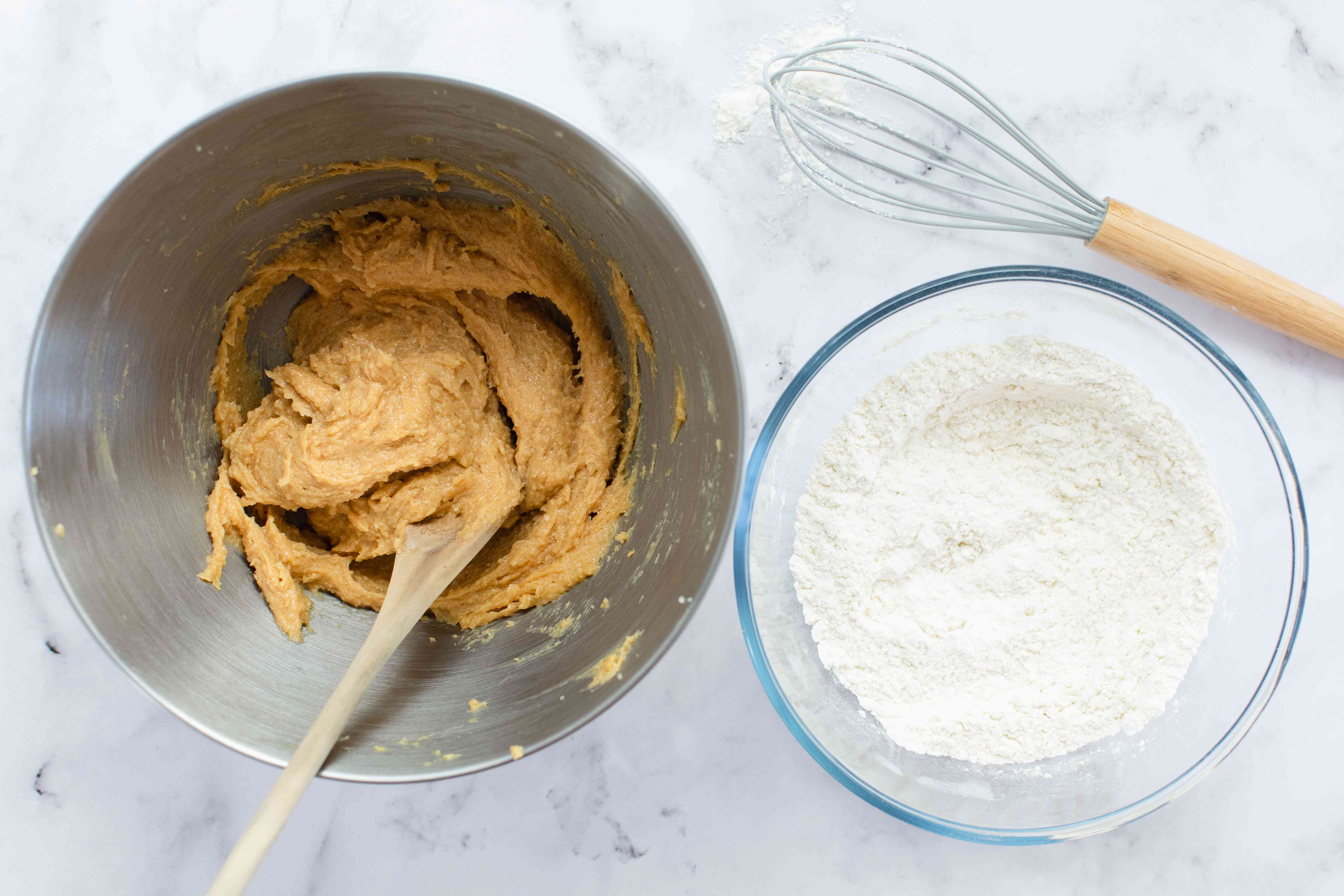 Peanut butter in a metal bowl with flour in a glass bowl next to it.