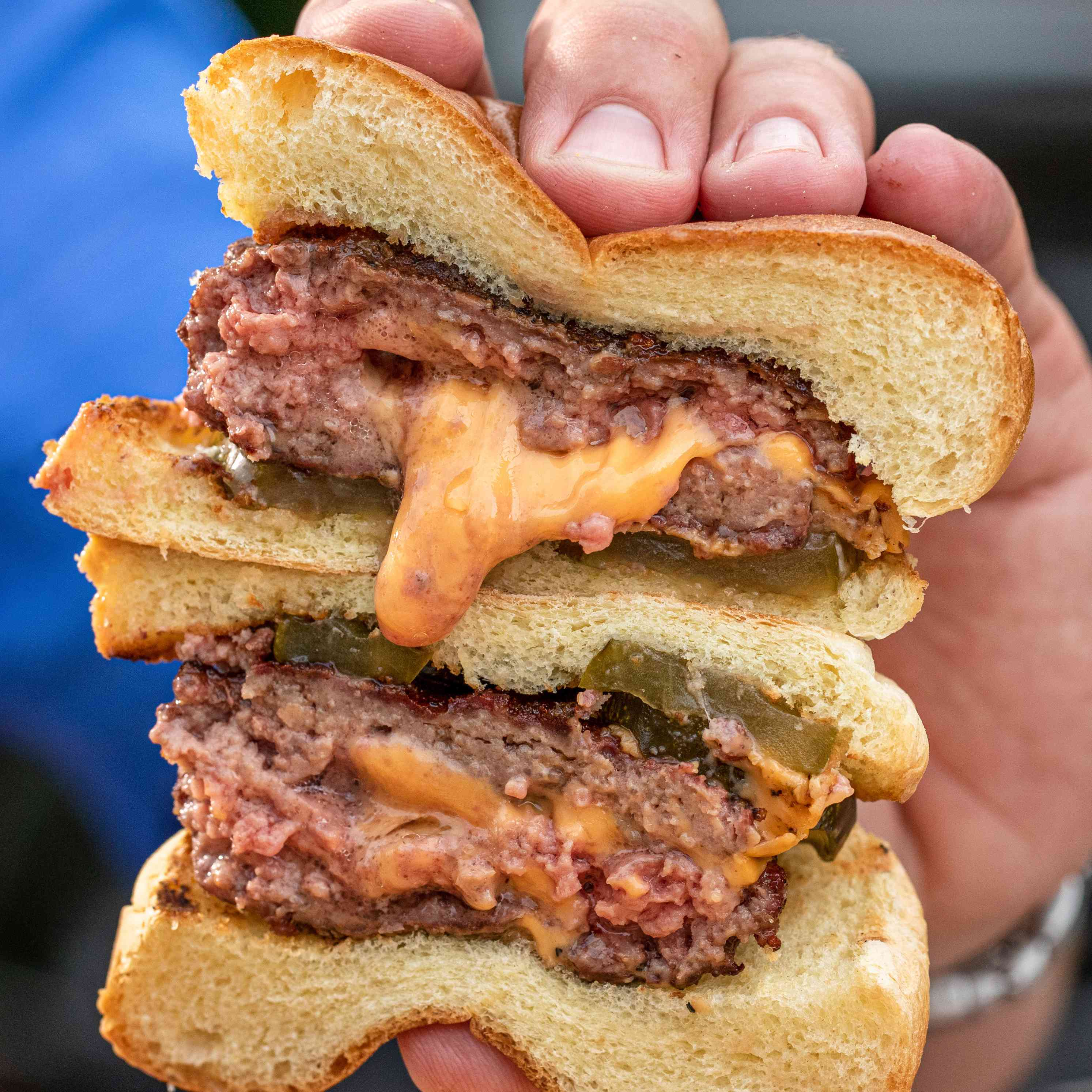 Jucy Lucy hamburger cut in half and held on top of each other in a hand.