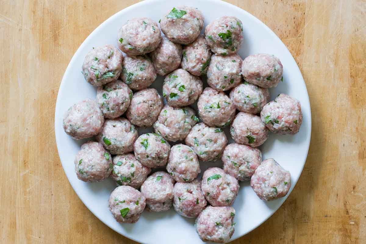 Authentic italian wedding soup meatballs formed and set on a plate.