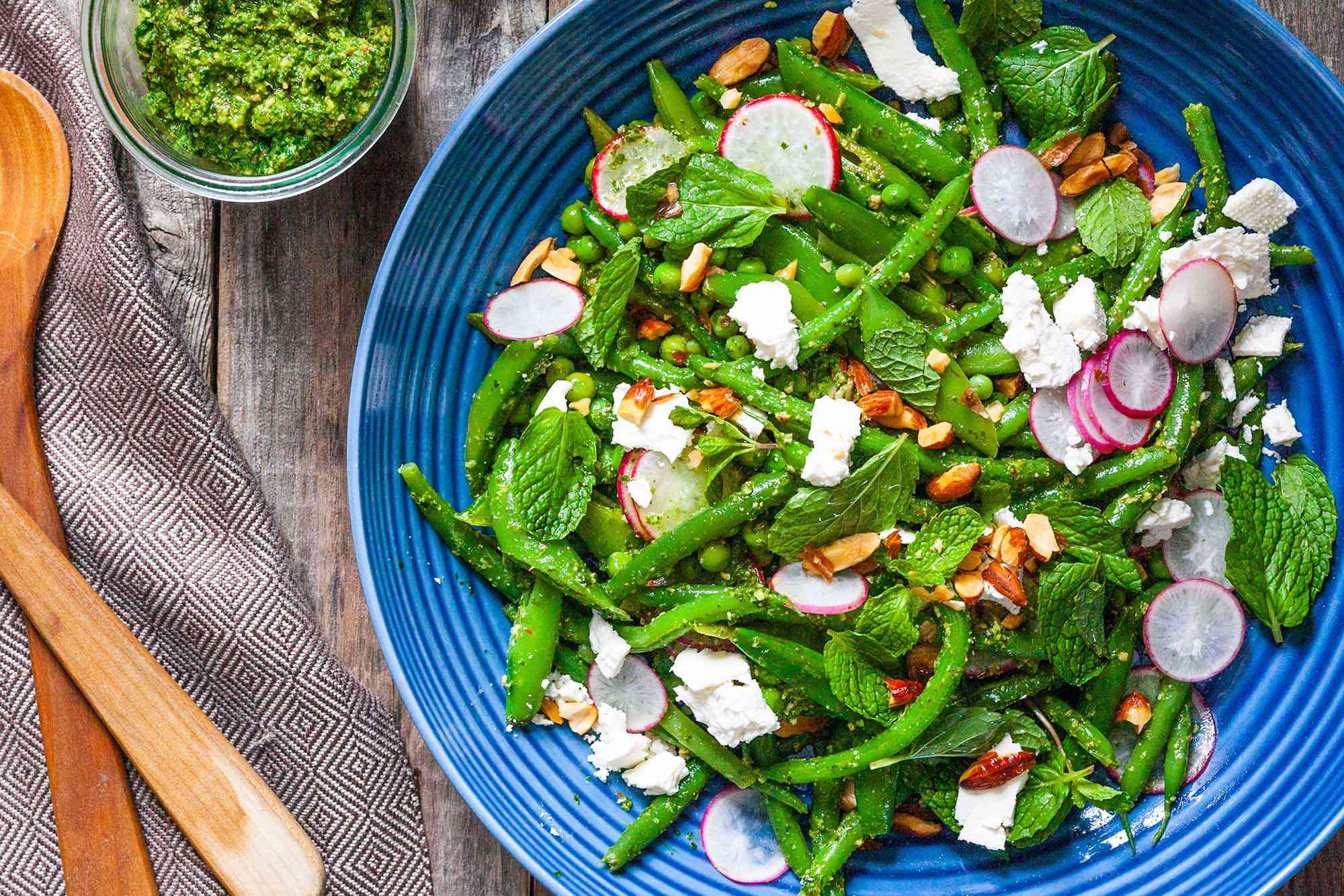 Spring Salad with Radishes - blue bowl with a salad of green beans, radish and on a wood table.
