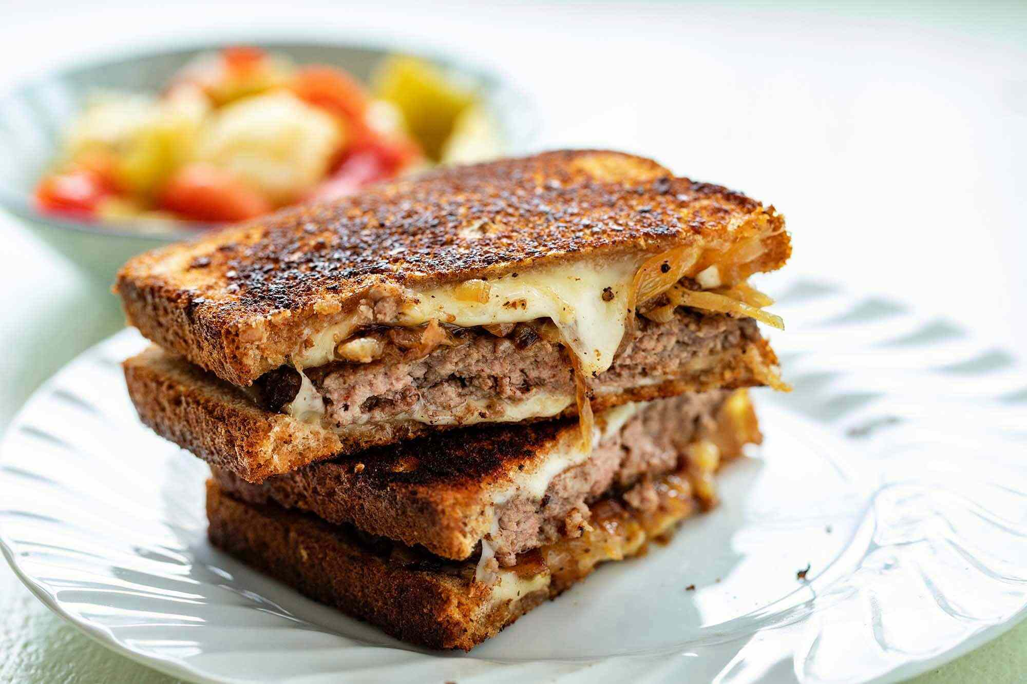 Two halves of a patty melt stacked on top of each other with gooey cheese