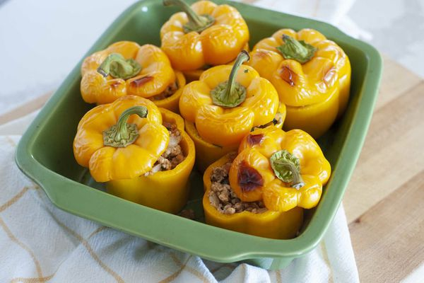 A casserole dish with six yellow bell peppers to show how to make stuffed peppers.