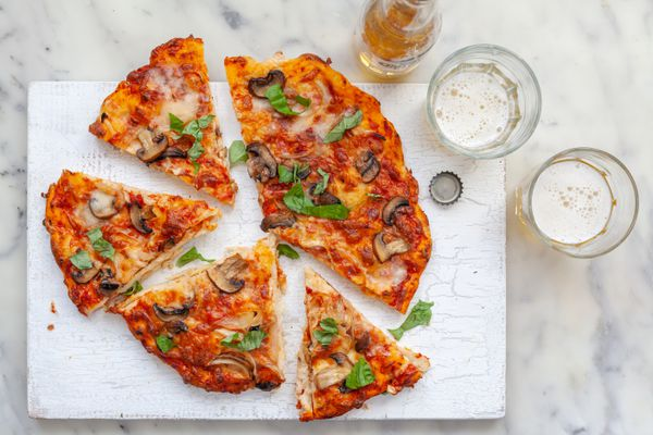 Pizza ingredients on a pizza cut into slices.