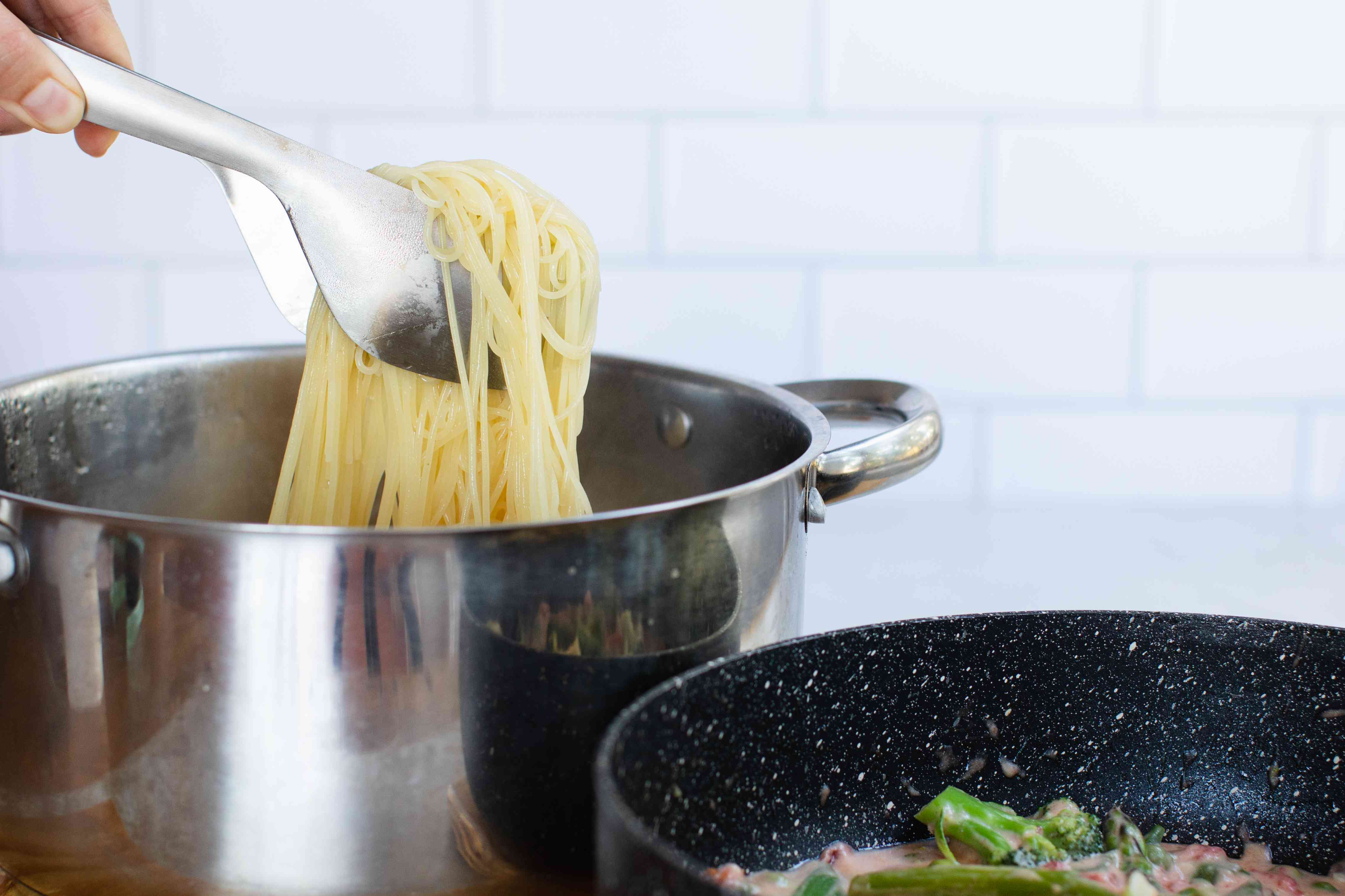 Tongs with cooked spaghetti noodles in a pot with a the pasta primavera vegetables next to it in a skillet.