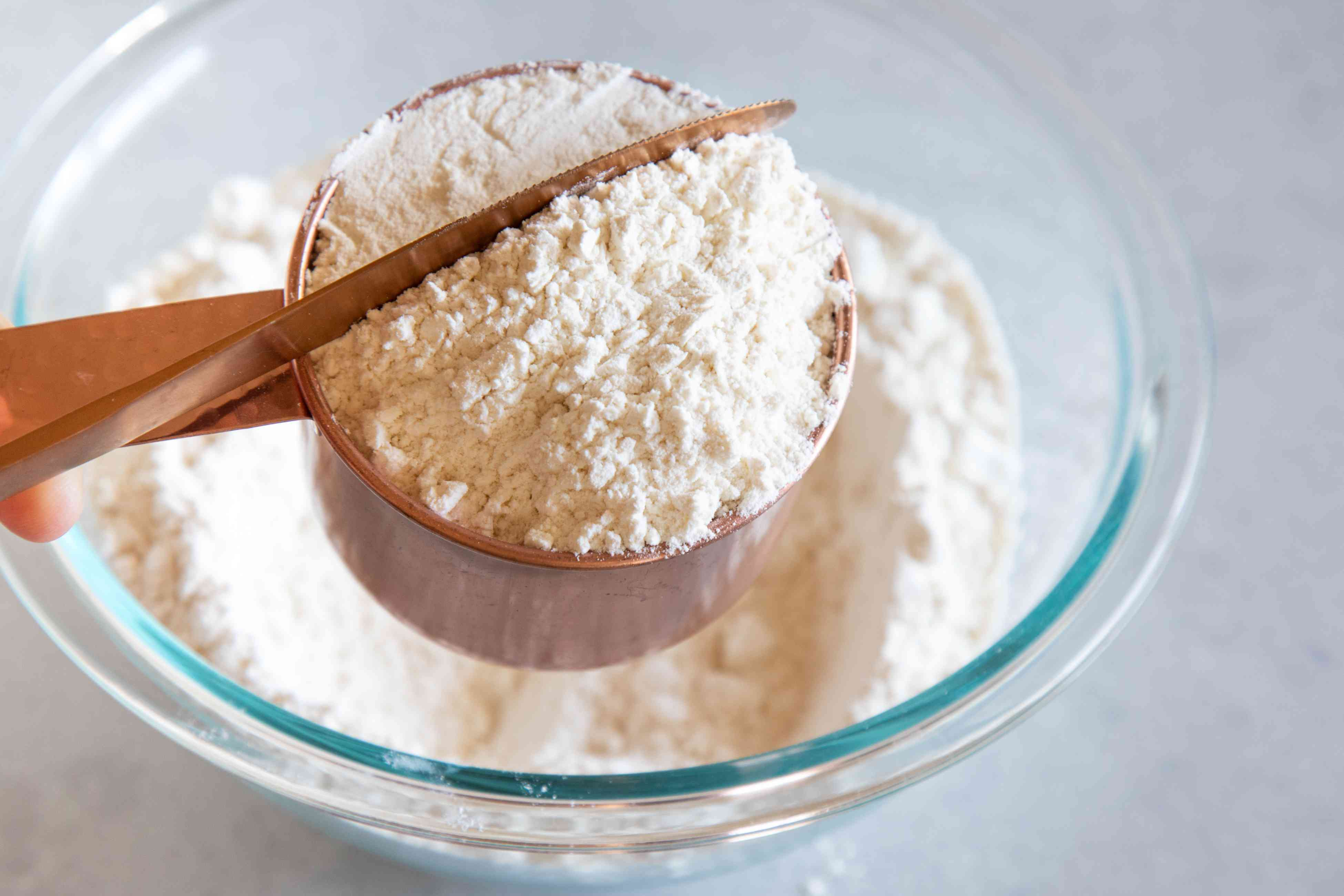 How to measure flour by using a knife to level off the heaping cup of flour.