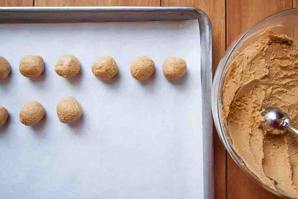 Filling for Peanut butter palls set rolled into balls and set on a baking tray covered in parchment.