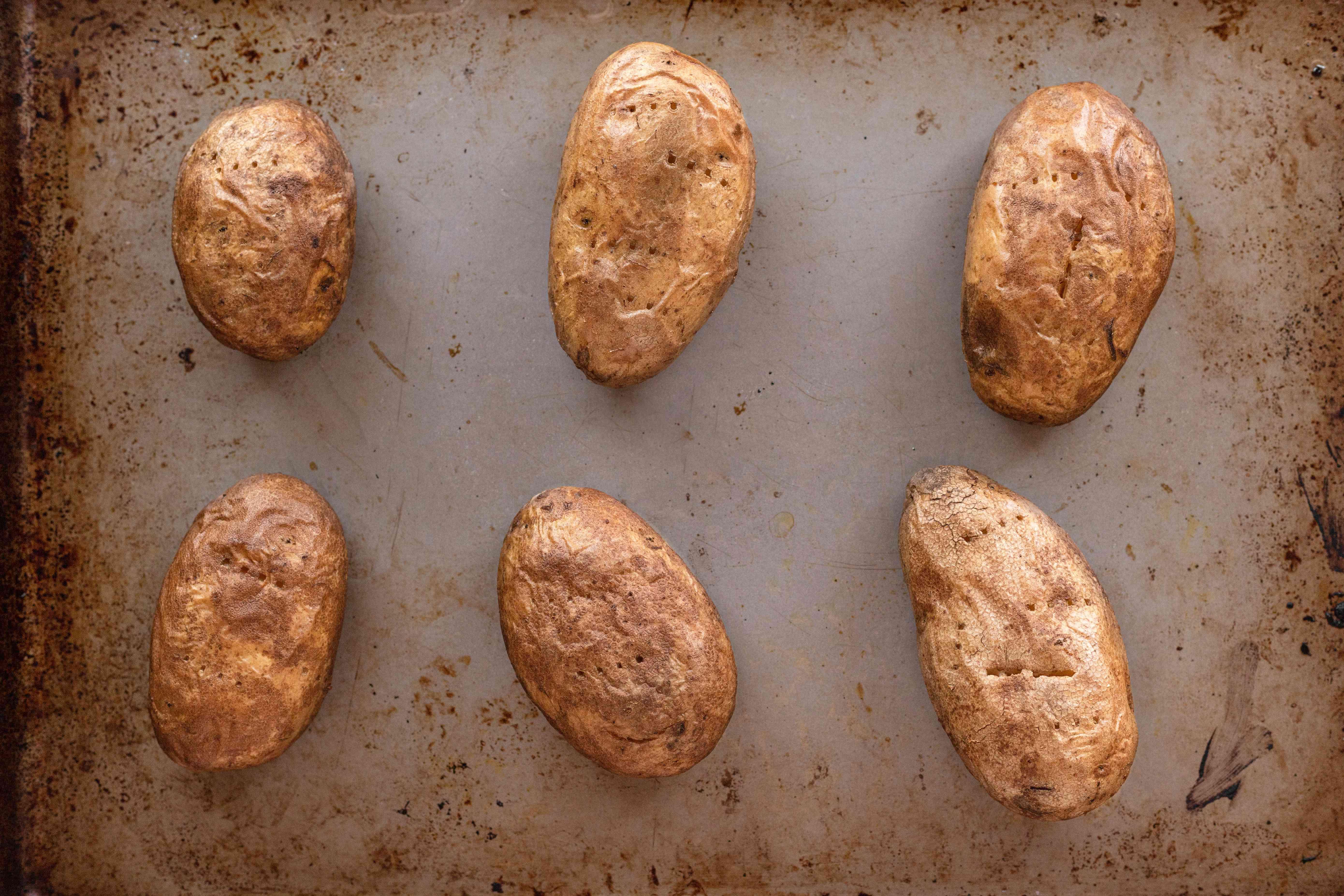 Potatos halved on a baking sheet to make a potato skins recipe.