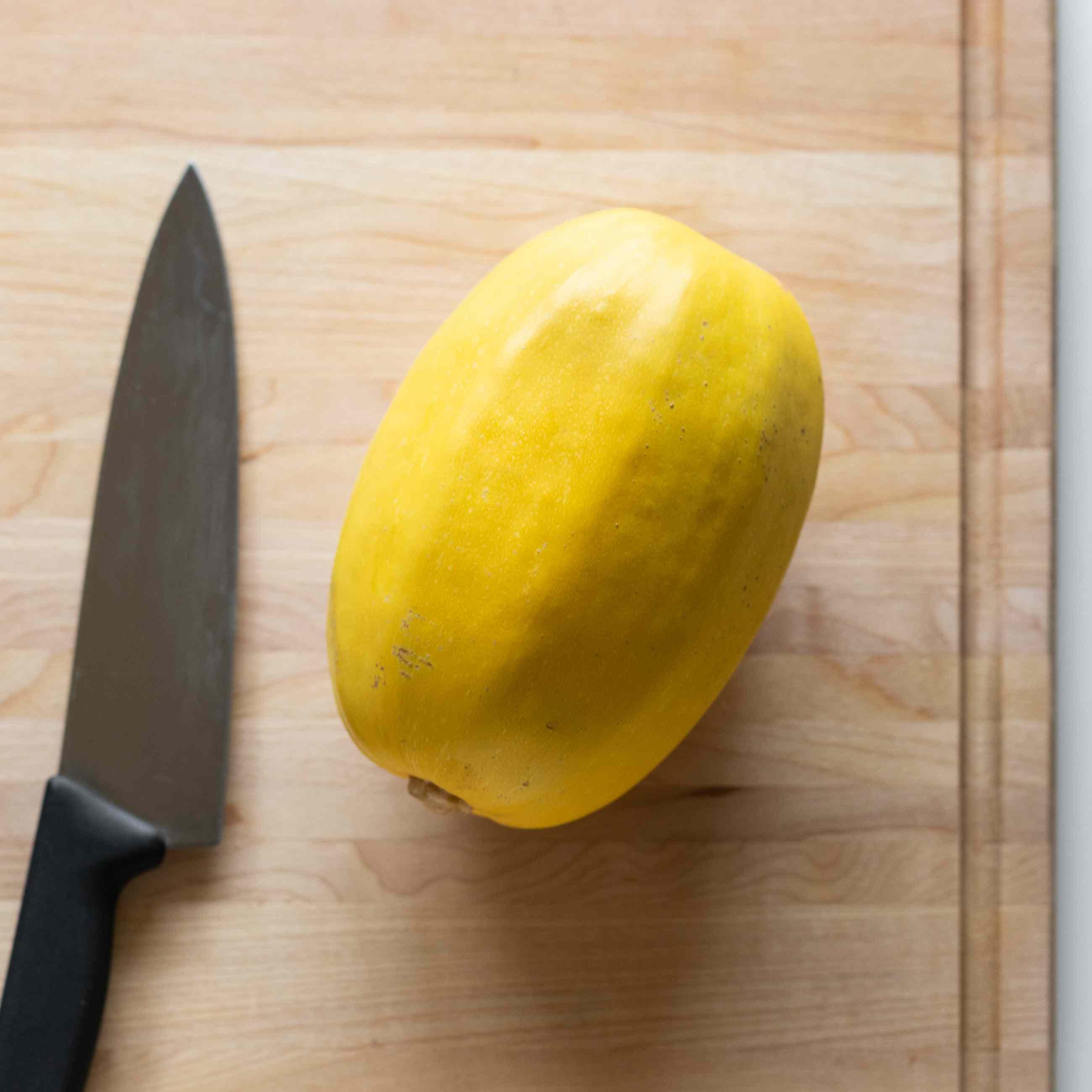 Whole spaghetti squash and chef's knife on wood cutting board