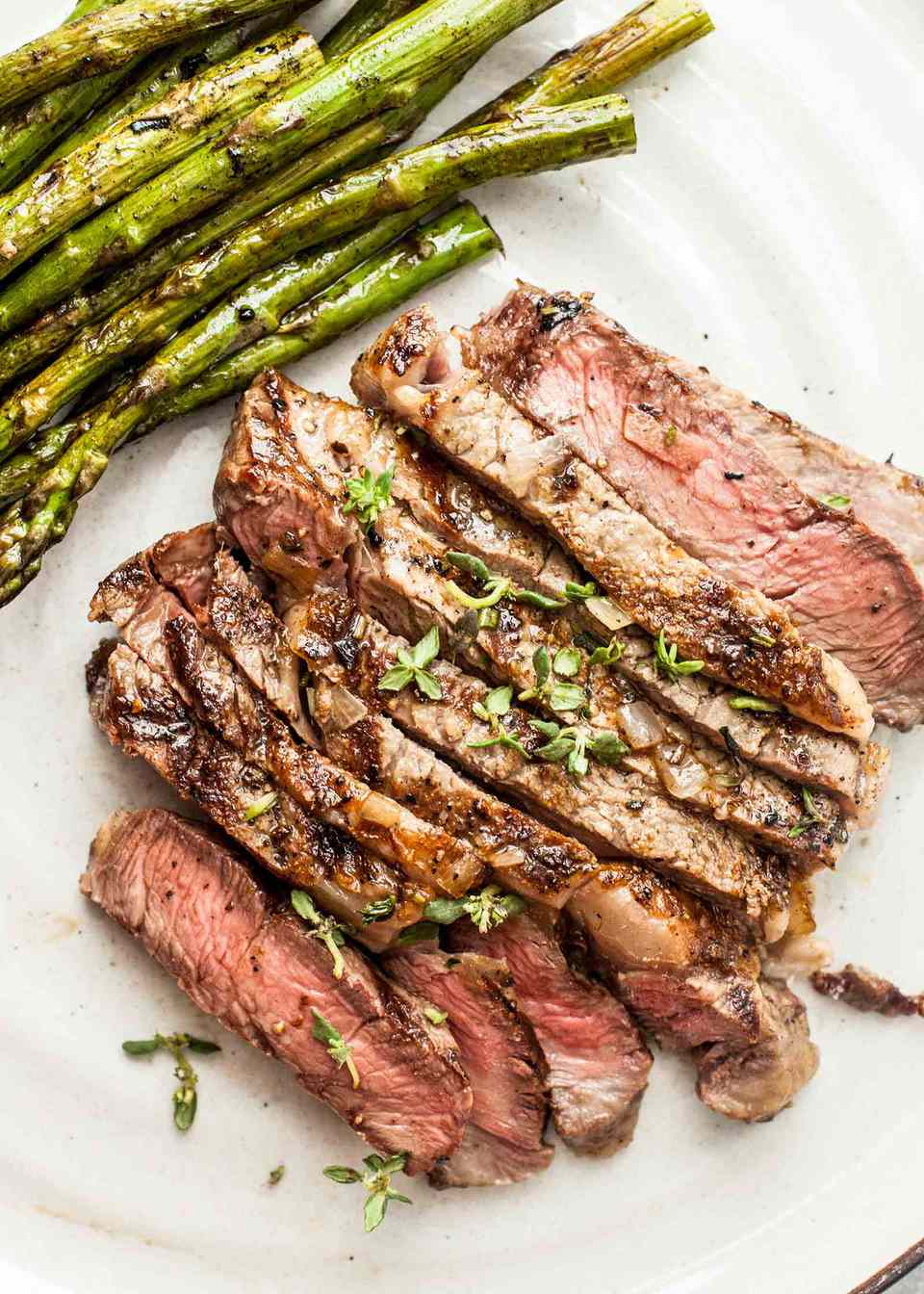 Grilled steak sliced and served on a platter with asapragus