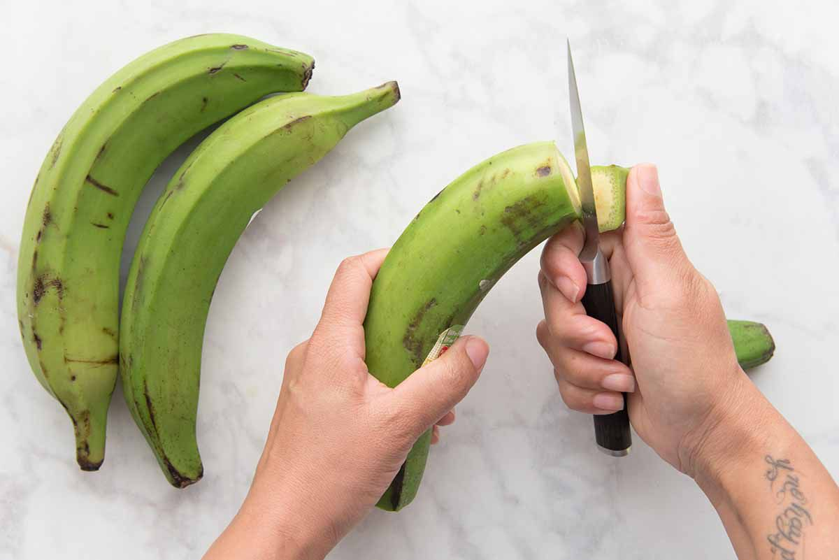 Person cutting the top off of a green plaintain.