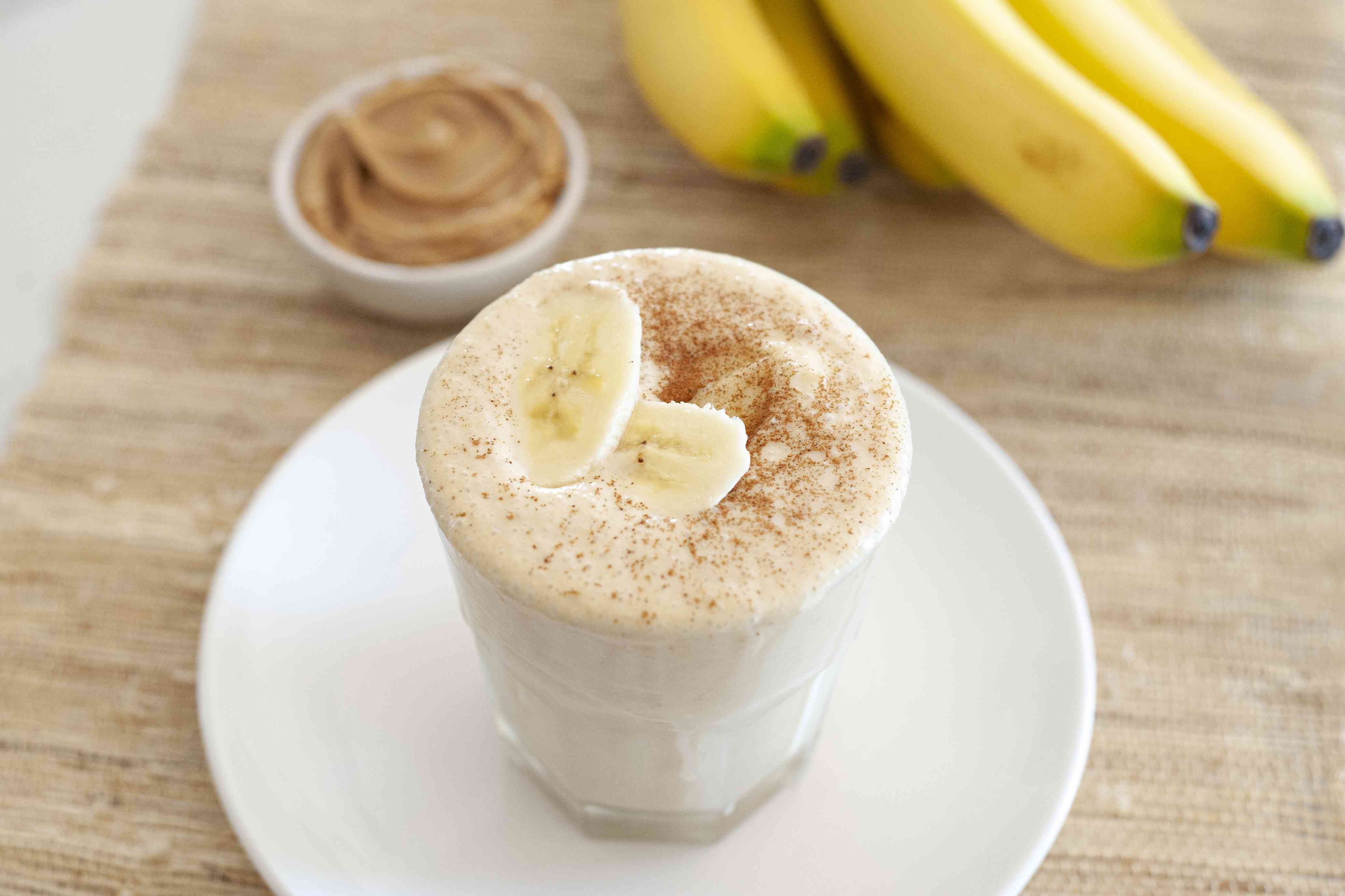BEST peanut butter banana smoothie in a cup set on a plate on a cutting board.