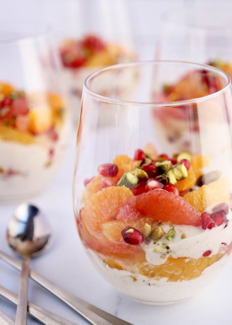 Glass of citrus fruits and yogurt topped with seeds and nuts on a white surface.