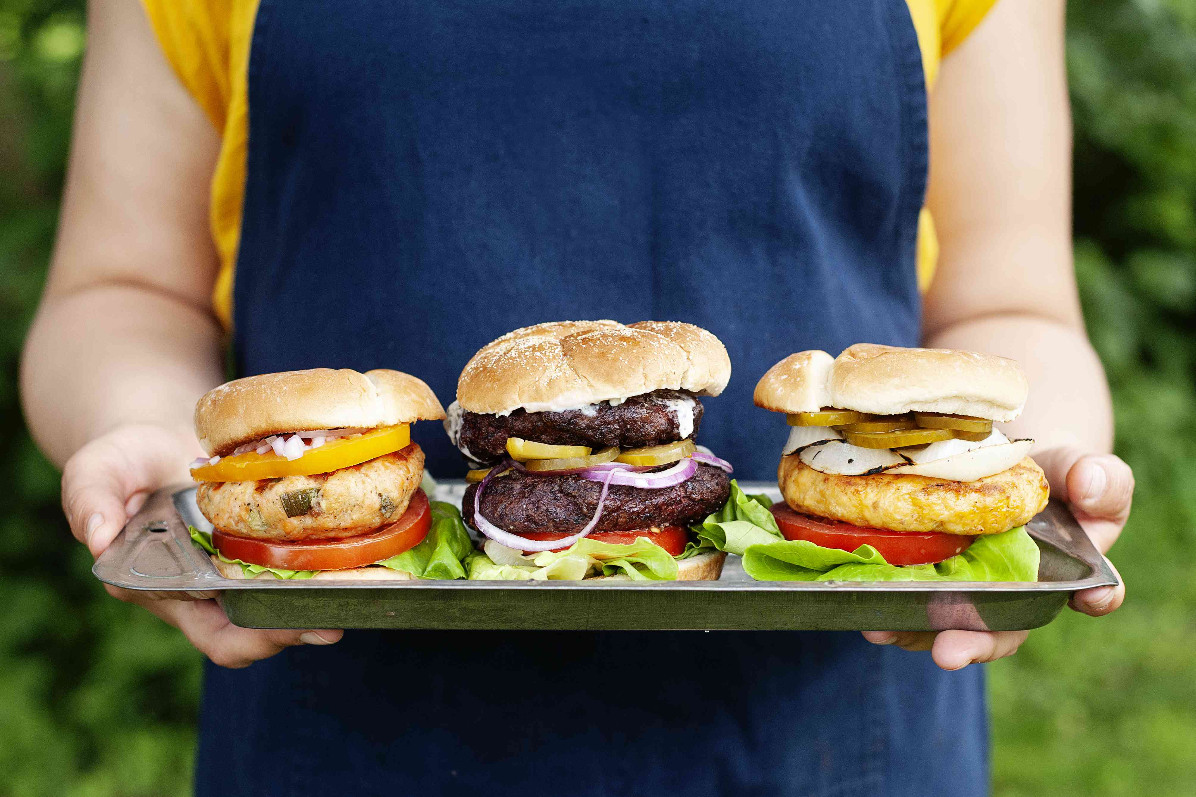 A woman in a blue apron holding 3 burgers on a tray. One is beef, one is chicken and one is salmon. They all have vegetable and are on a buns.