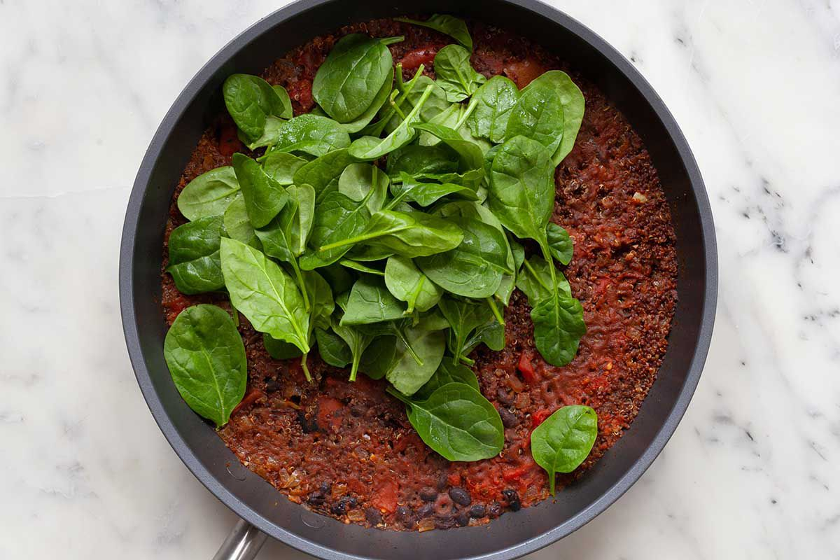 Saute pan with mexican-style black bean skillet dinner in it and spinach on the top.