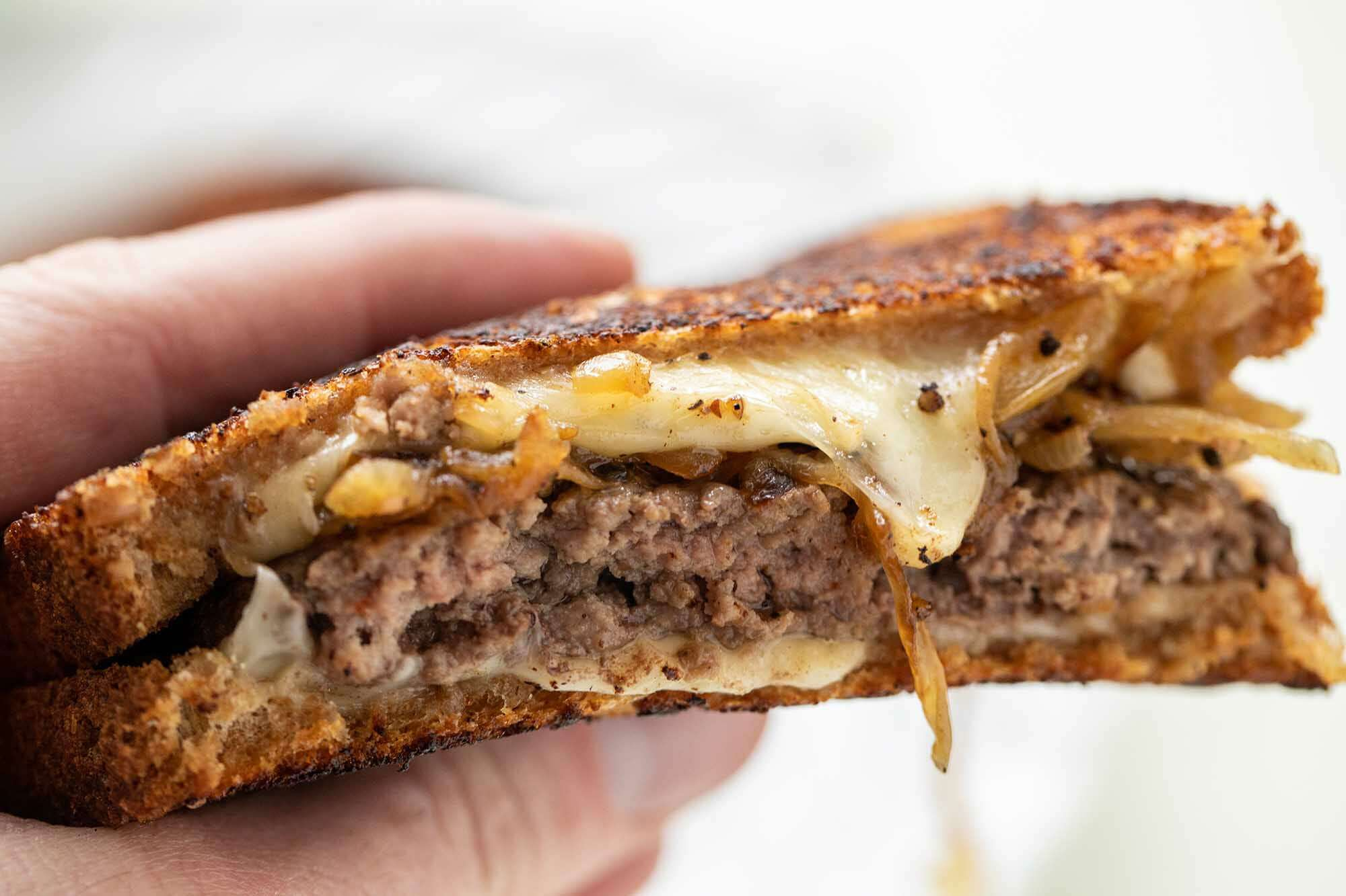 Perfect patty melt held in a hand with the melted cheese, caramelized onions and beef patties visible.