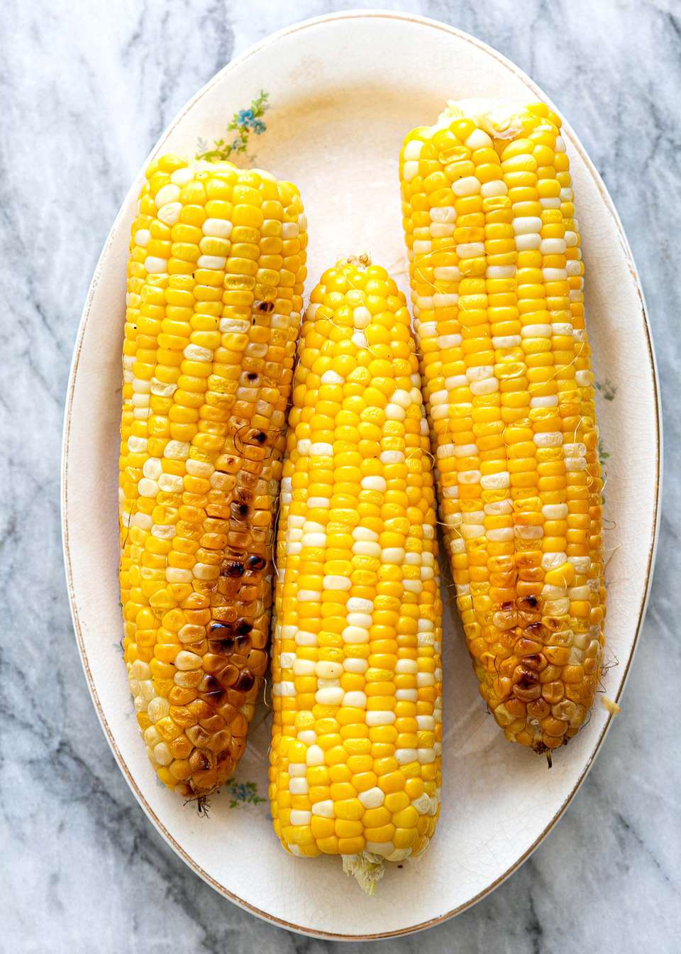 Corn on the cob, grilled, served on an oval platter