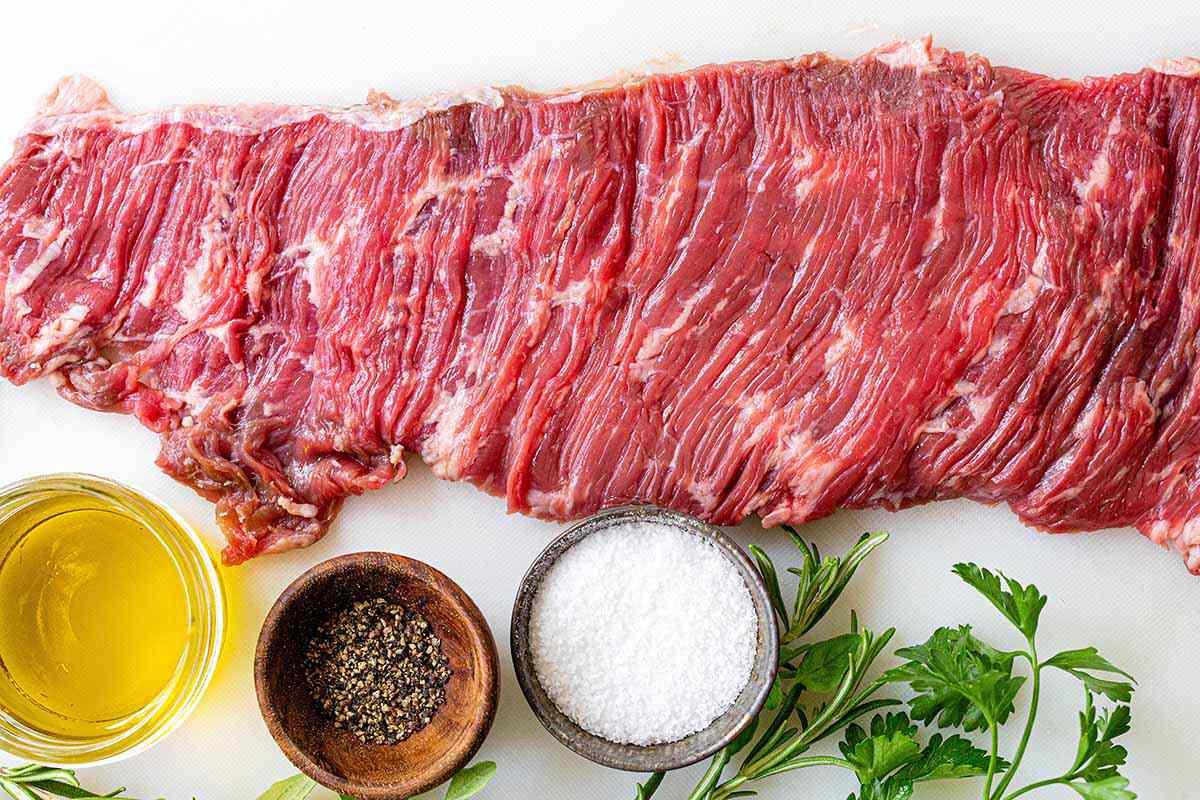 Easy Skirt Steak Recipe - steak on cutting board with salt, pepper, and herbs