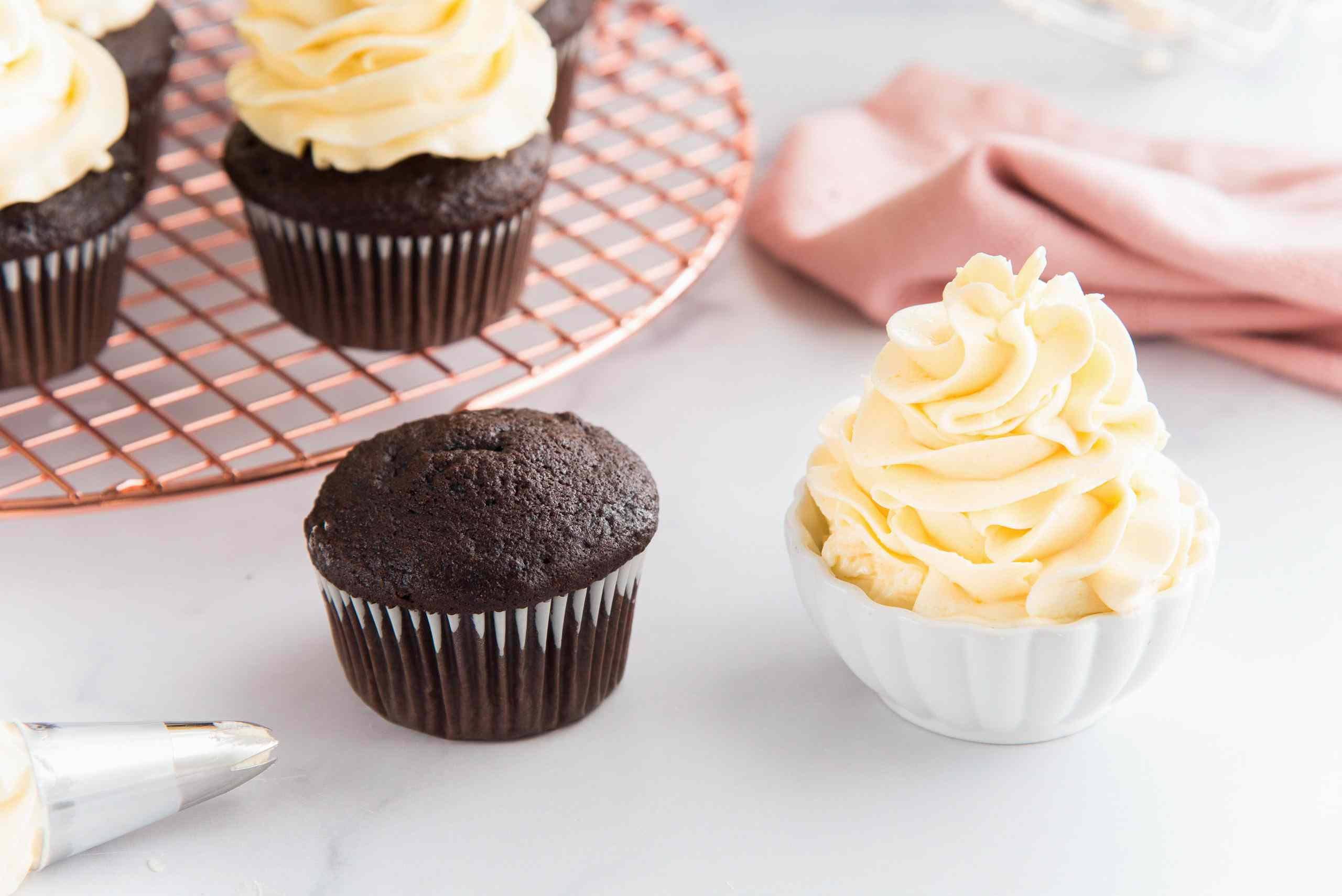 The best French buttercream piped in a small bowl and chocolate cupcakes to the left.