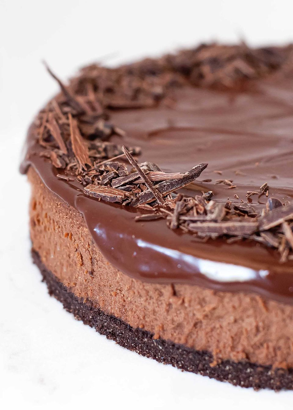 Close up of a chocolate cheeescake with dripping ganache frosting and shards of chocolate on top