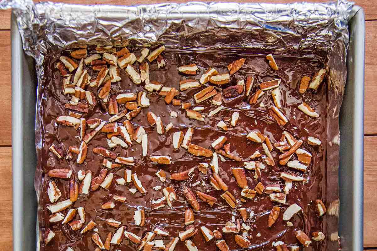 Toffee sprinkled with pecans in a foil lined baking sheet.