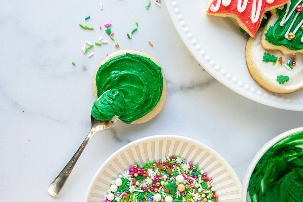 Green frosting and festive sprinkles for holiday cookies