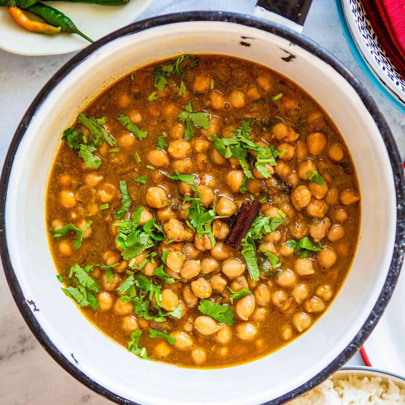 Best Chana Masala - chana masla in pot with fresh green herbs sprinkled on top.