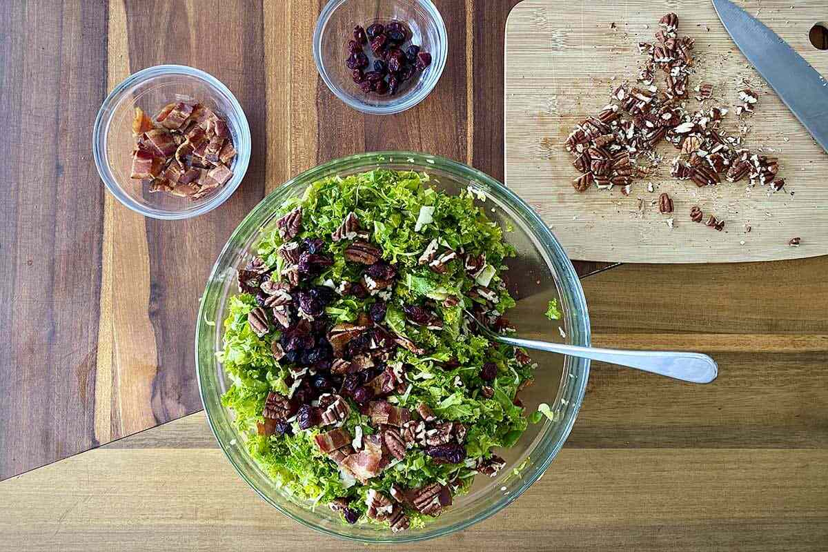 A mixing bowl of Raw Kale and Shaved Brussels Sprout Salad with Maple Dijon Vinaigrette with chopped bacon and pecans above the bowl.