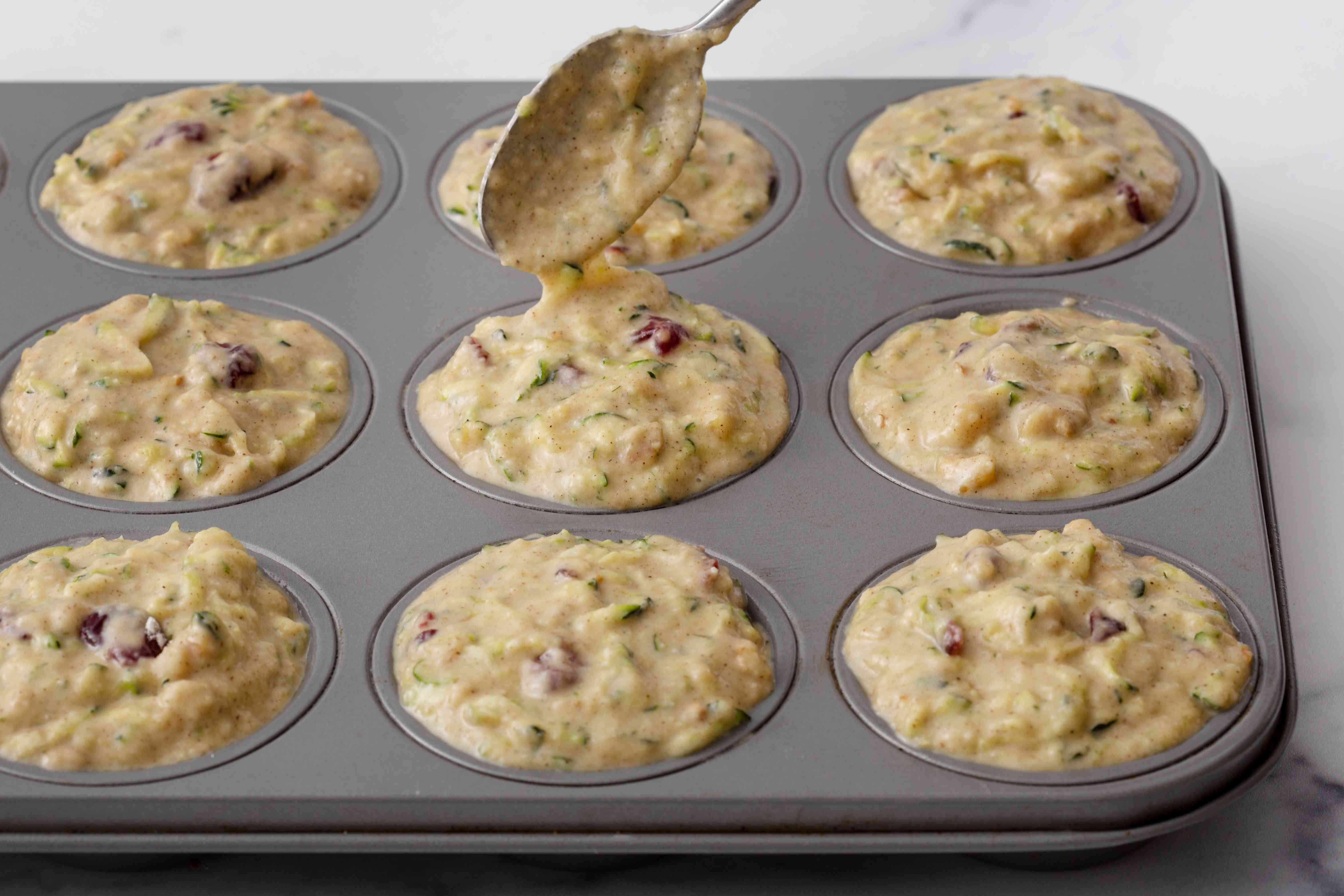 Spooning batter into a muffin tin to make a zucchini muffin recipe.