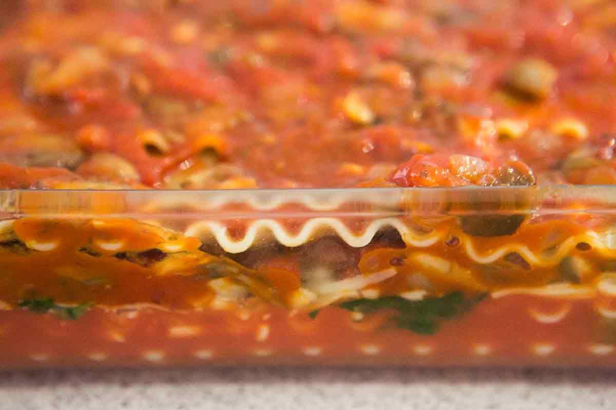 Vegetable lasagna layers seen through pyrex dish