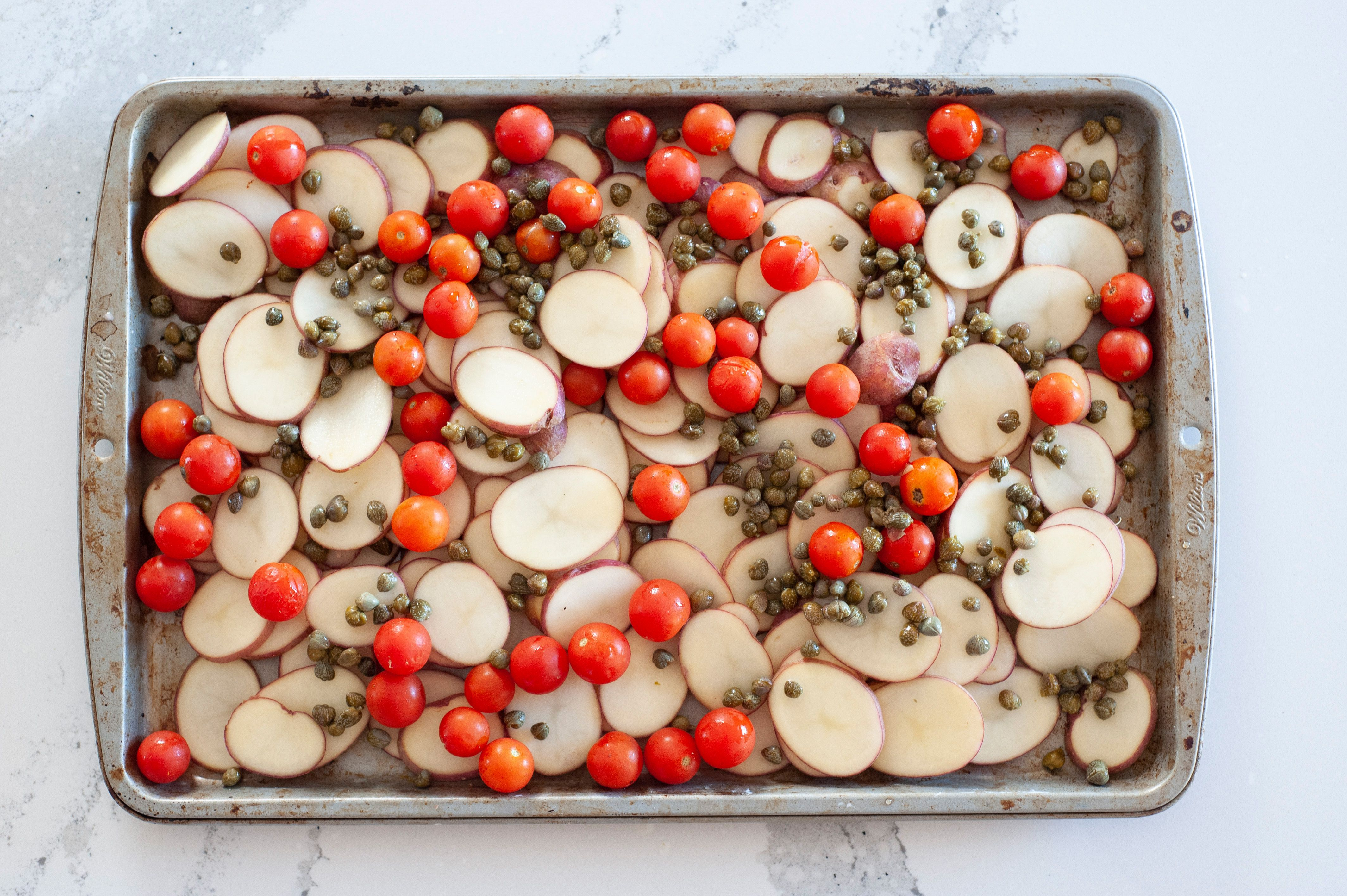 Overhead view of a sheet pan with potatoes and cherry tomatoes.