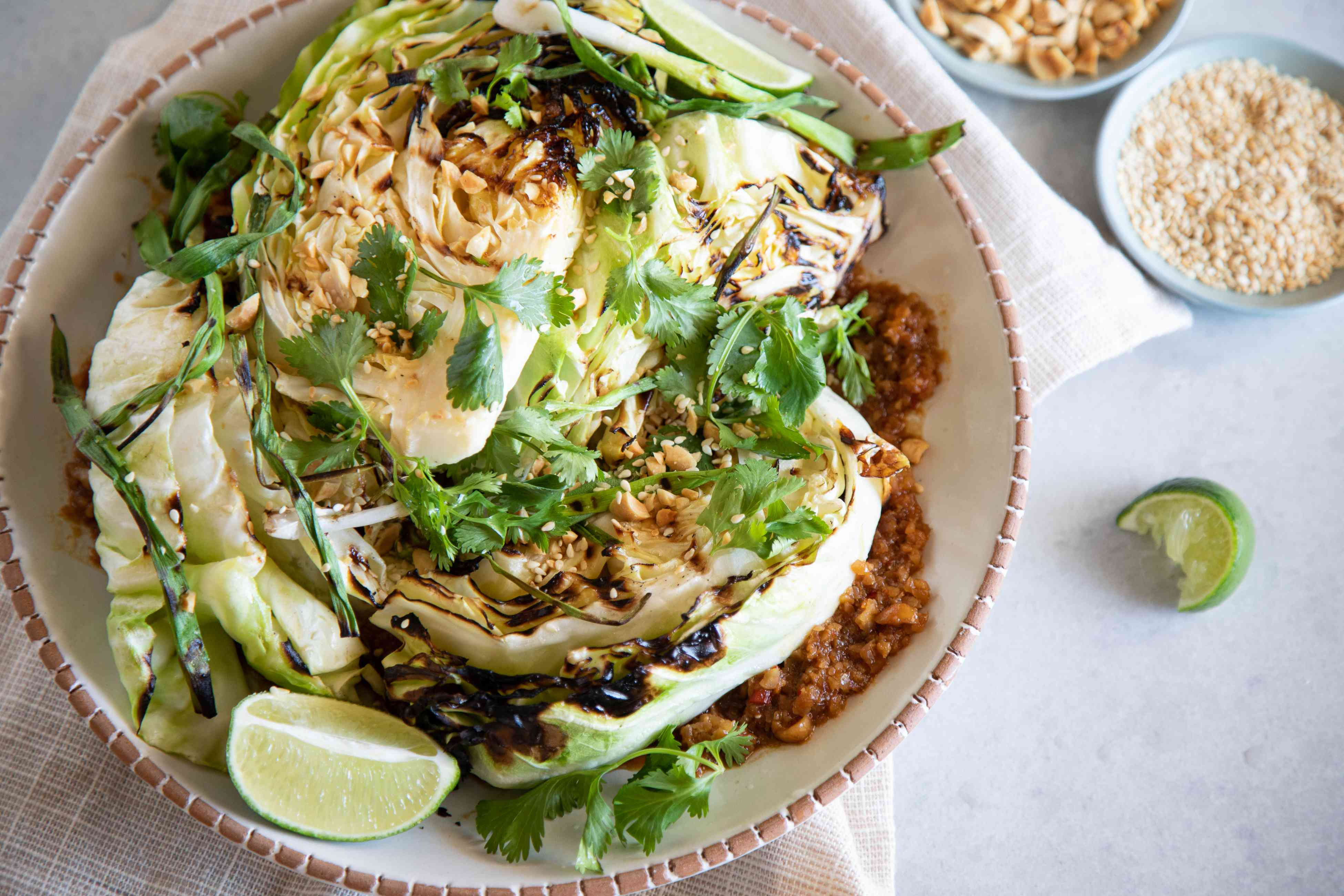 Grilled cabbage with peanut satay sauce on a plate with toppings in small bowls around it.