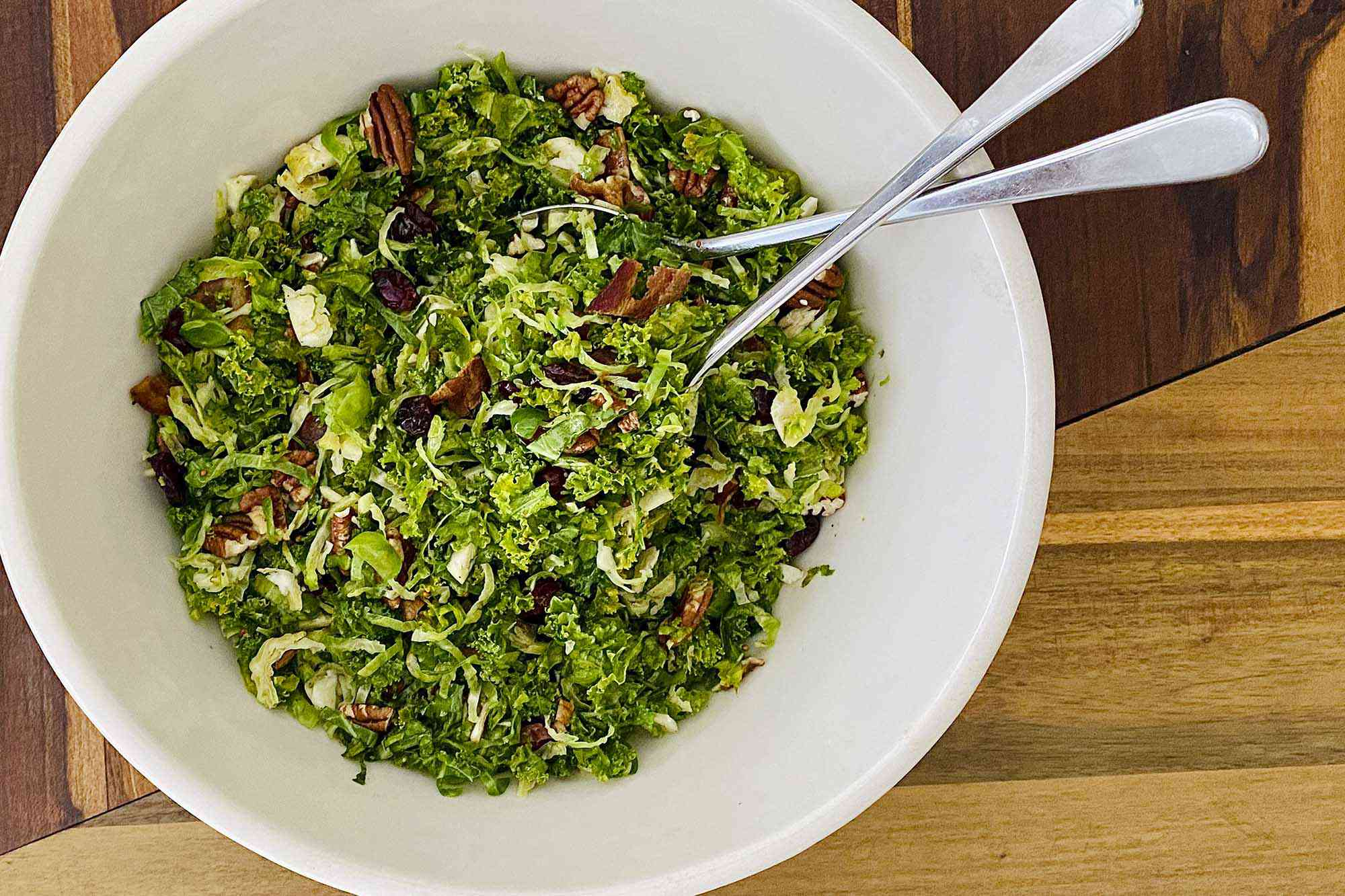 A serving bowl with Raw Kale and Shaved Brussels Sprout Salad with Maple Dijon Vinaigrette ready to be served.