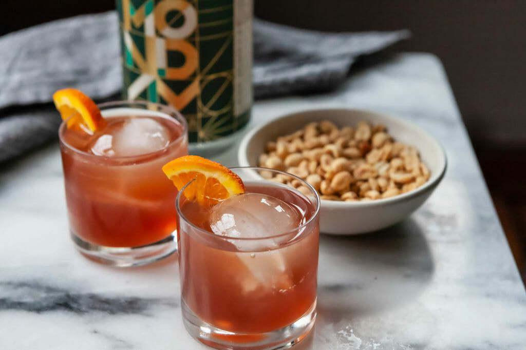 Two alcohol free negronis in rocks glasses with an orange wedge and bar nuts.