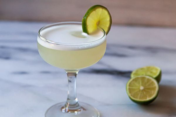 A chilled coupe with a frothy gin cocktail to show what a gimlet is.